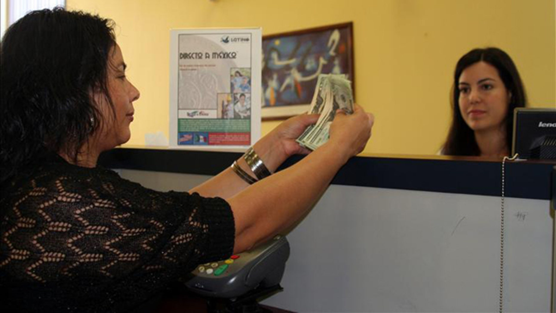 A Mexican woman (left) deposits money into her account in Charlotte, North Carolina. EFE/File