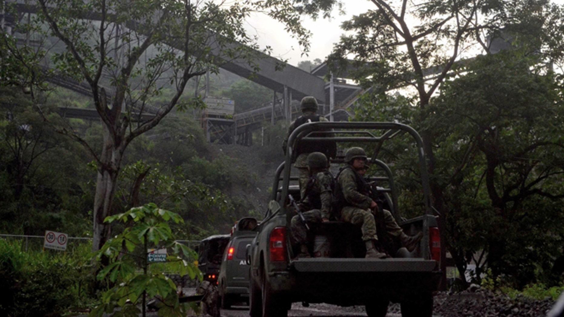In this Aug. 14, 2013 photo, Mexican army soldiers enter the iron ore mine in the town of Aquila, Mexico. A resident of Aquila, said that since 2012, the Knights Templar cartel demanded residents hand over part of the royalty payments from the local iron ore mine operated by Ternium, a Luxembourg-based consortium. Mexican drug cartels long ago moved into oil theft, pirated goods, extortion and kidnapping, but it still came as a shock this month when federal officials revealed the gangs have broadened the scope and sophistication of their economic empires by entering the country's lucrative mining industry, exporting iron ore to Chinese and other foreign mills. (AP Photo/Agencia Esquema)