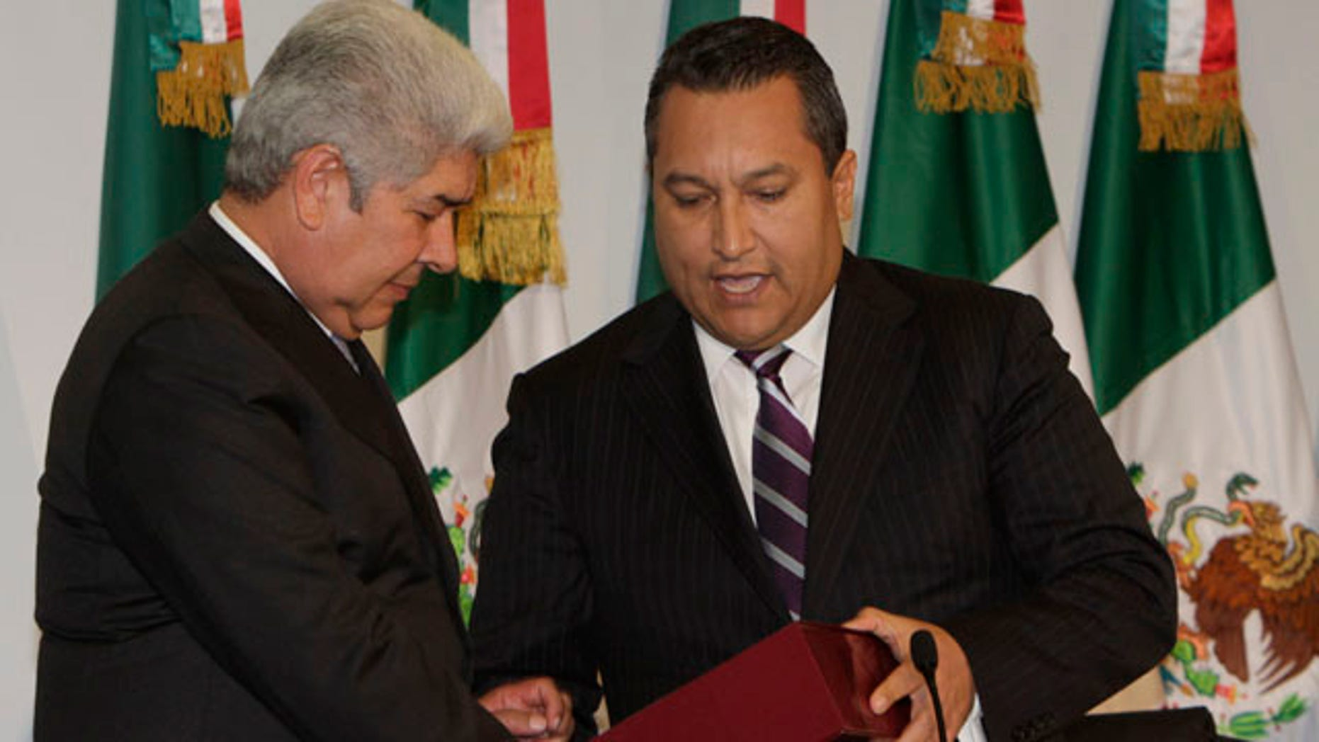 September 1: Mexico's Interior Secretary Jose Francisco Blake, hands the government's annual state of the nation report to Lower House President Francisco Ramirez Acuna at Congress in Mexico City. (AP)