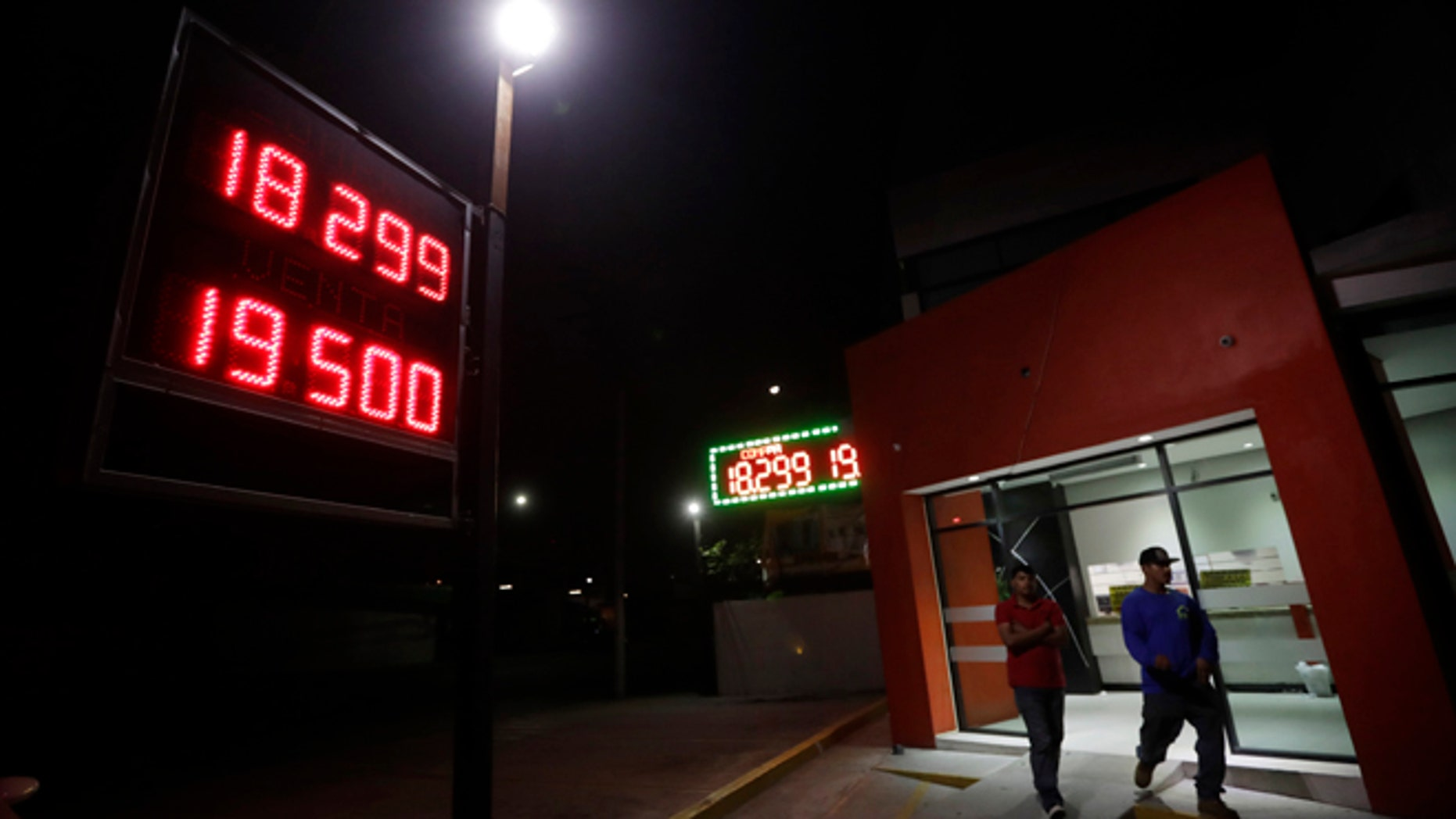 A currency exchange business displays rates of the Mexican peso Tuesday, Nov. 8, 2016, in Tijuana, Mexico.