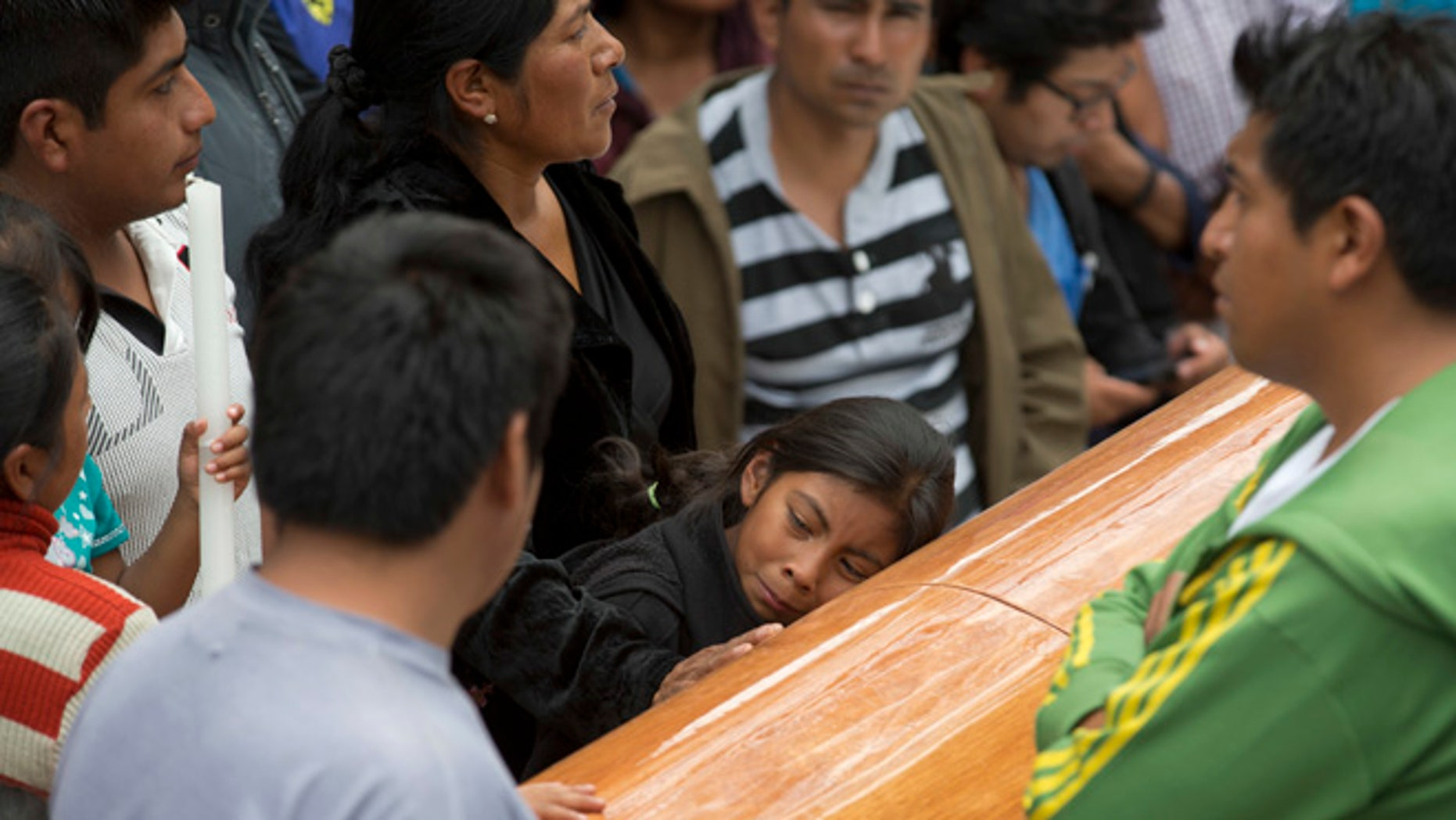 A girl embraces the coffin with the body of Yalid Jimenez, 29, who died yesterday during the clearing of the highway in Nochixtlan, Mexico, Monday, June 20, 2016. Violence erupted during the weekend in which six people died in confrontations between the police and striking teachers. The teachers are protesting against plans to overhaul the country's education system which include federally mandated teacher evaluations. (AP Photo/Eduardo Verdugo)