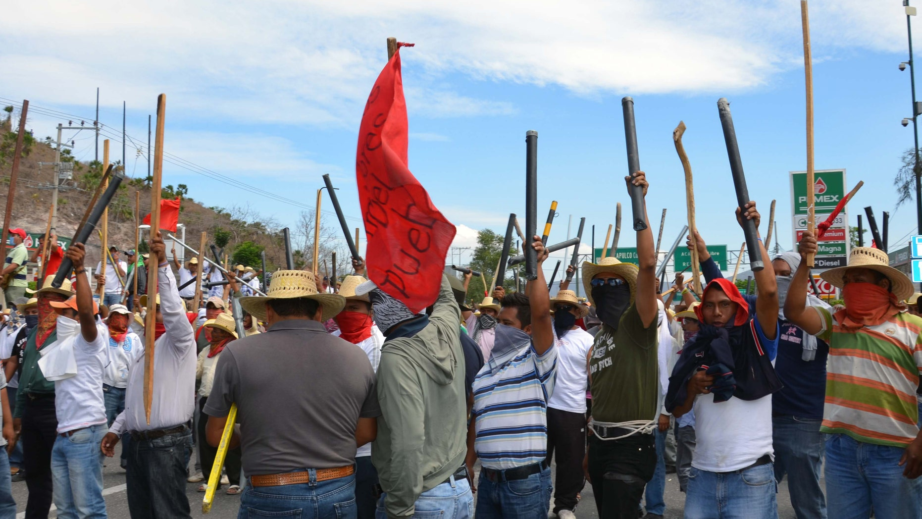 Teachers chant slogans holding up metal pipes and wooden sticks while blocking a major highway in Chilpancingo, Mexico, Thursday, April 11, 2013. (AP Photo/Alejandrino Gonzalez)