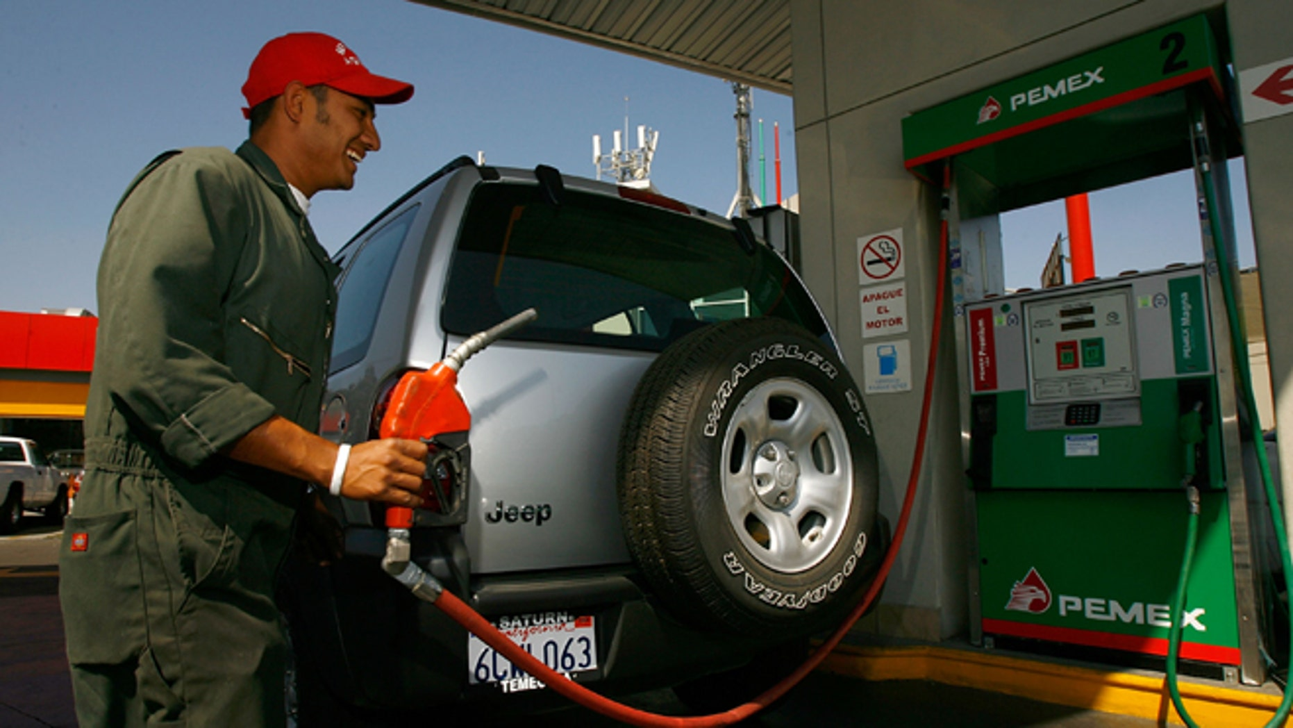 TIJUANA, MEXICO - JUNE 27:  A Pemex gas station attendant fills a car registered with California license plates on June 27, 2008 in Tijuana, Mexico. With the cost of gasoline in California around $4.60 per gallon, many drivers are buying their fuel in Mexico for about $3.20. There is a price to pay for cheaper gas though. Mexican gas is formulated with more sulfur than California gas and that can damage the emission control equipment on US cars, causing them to fail emissions tests and leading to expensive repairs. In addition, unless a driver has other business in Mexico, part of their fuel savings will be burned up idling in a line that can easily last for hours to get back into the US.  (Photo by David McNew/Getty Images)
