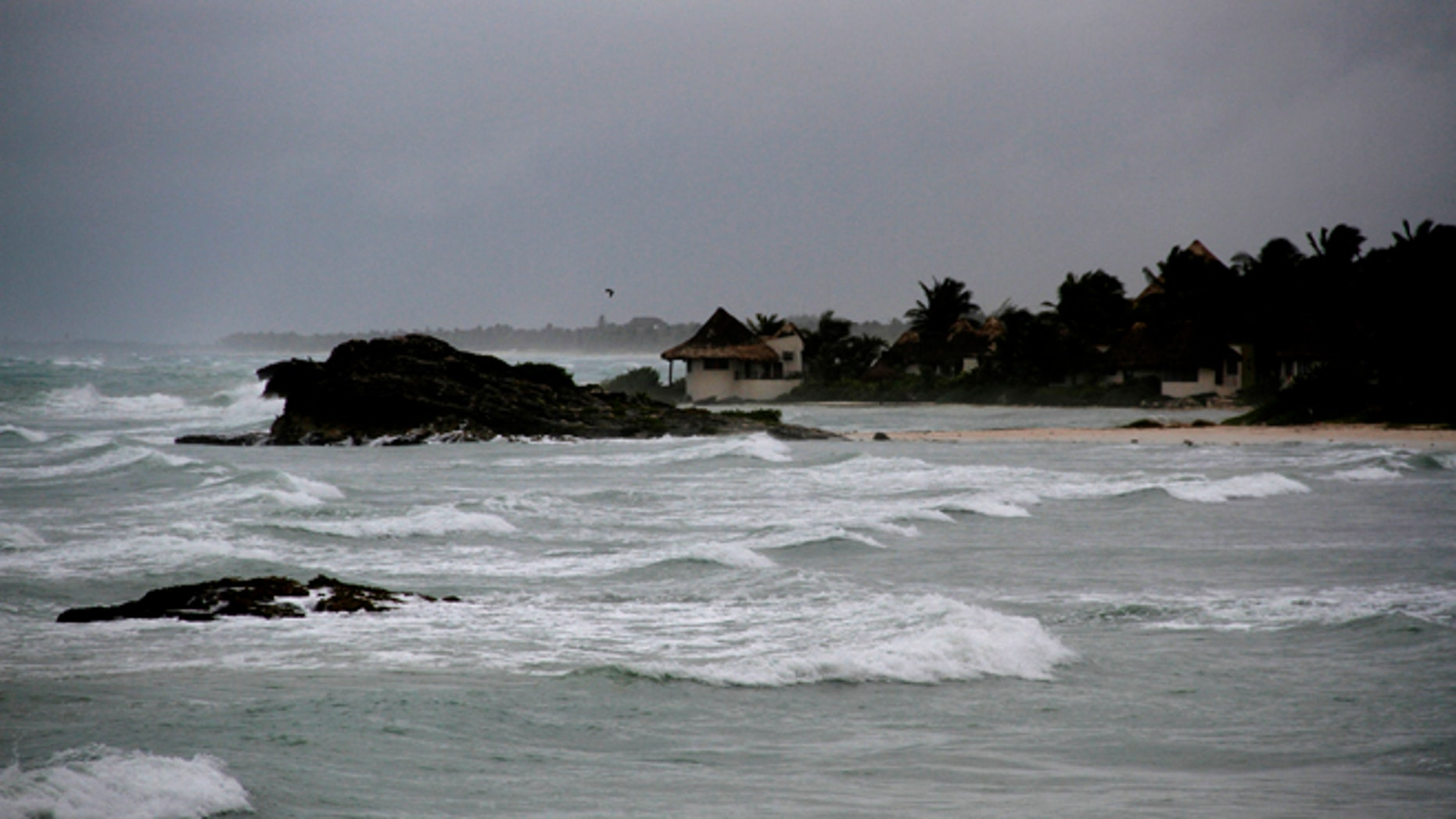 View of the beach in Tulum, Mexico, Tuesday, Aug. 7, 2012, as Tropical Storm Ernesto brings the threat of hurricane-force winds and torrential rains to the Caribbean coast. The heart of the storm was expected to hit south of Cancun and the Riviera Maya, though strong rain and winds were likely there, and officials prepared shelters there as a precaution. (AP Photo/Israel Leal)