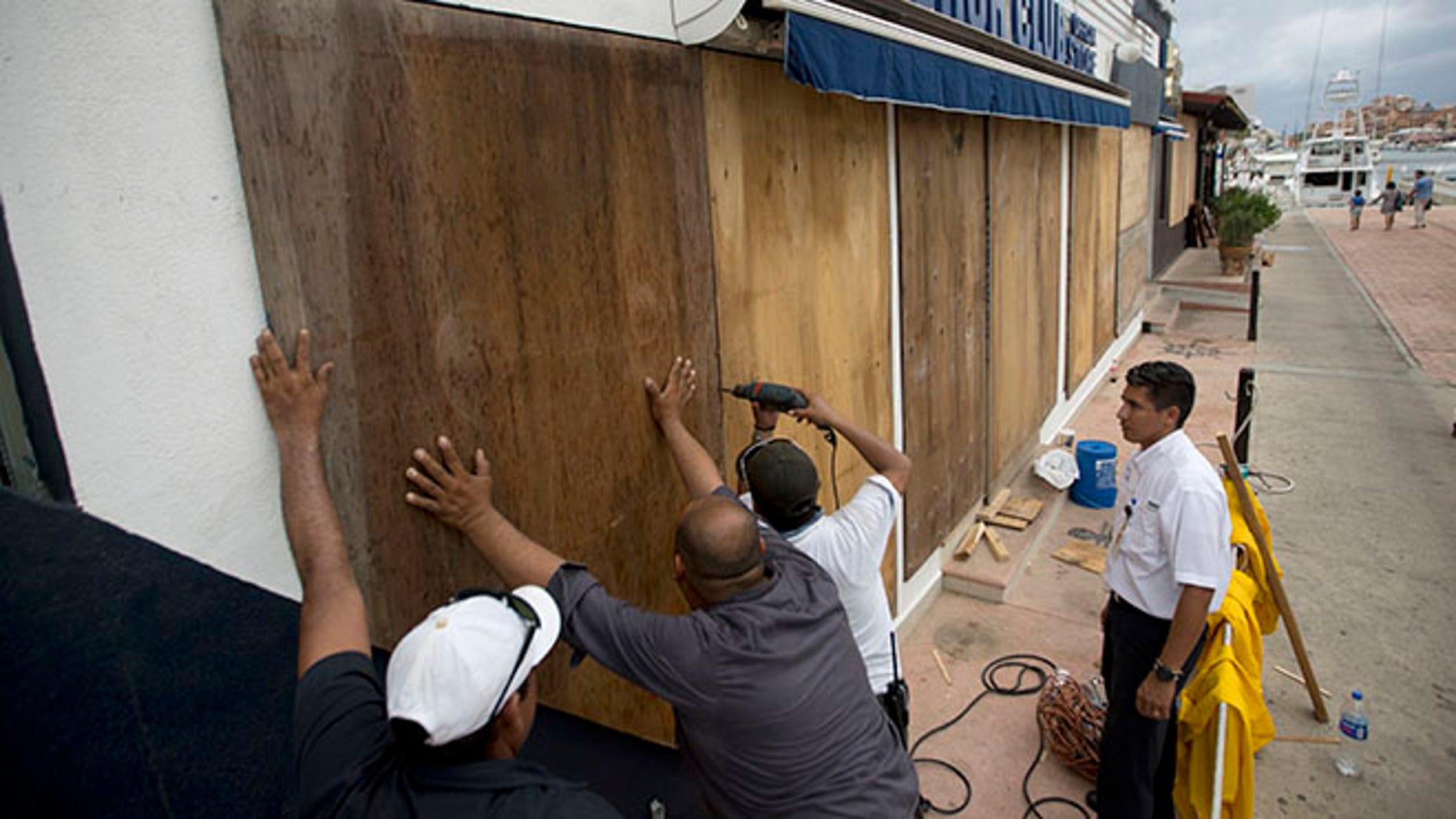 Workers board over a store front in preparation for Hurricane Newton, in Cabo San Lucas, Mexico, Monday Sept. 5, 2016. Authorities at the southern end of Mexico's Baja California peninsula ordered schools closed and set up emergency shelters as Hurricane Newton gained strength while bearing down on the twin resorts of Los Cabos for a predicted arrival Tuesday morning. (AP Photo/Eduardo Verdugo)