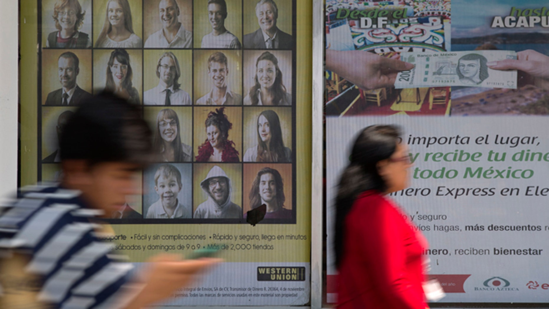 People walk past signs advertising money transfer services outside a business in Mexico City, Tuesday, April 5, 2016. U.S. Republican Presidential frontrunner Donald Trump is threatening to block billions of dollars in U.S. remittances to force Mexico to pay for his proposed border wall. (AP Photo/Rebecca Blackwell)