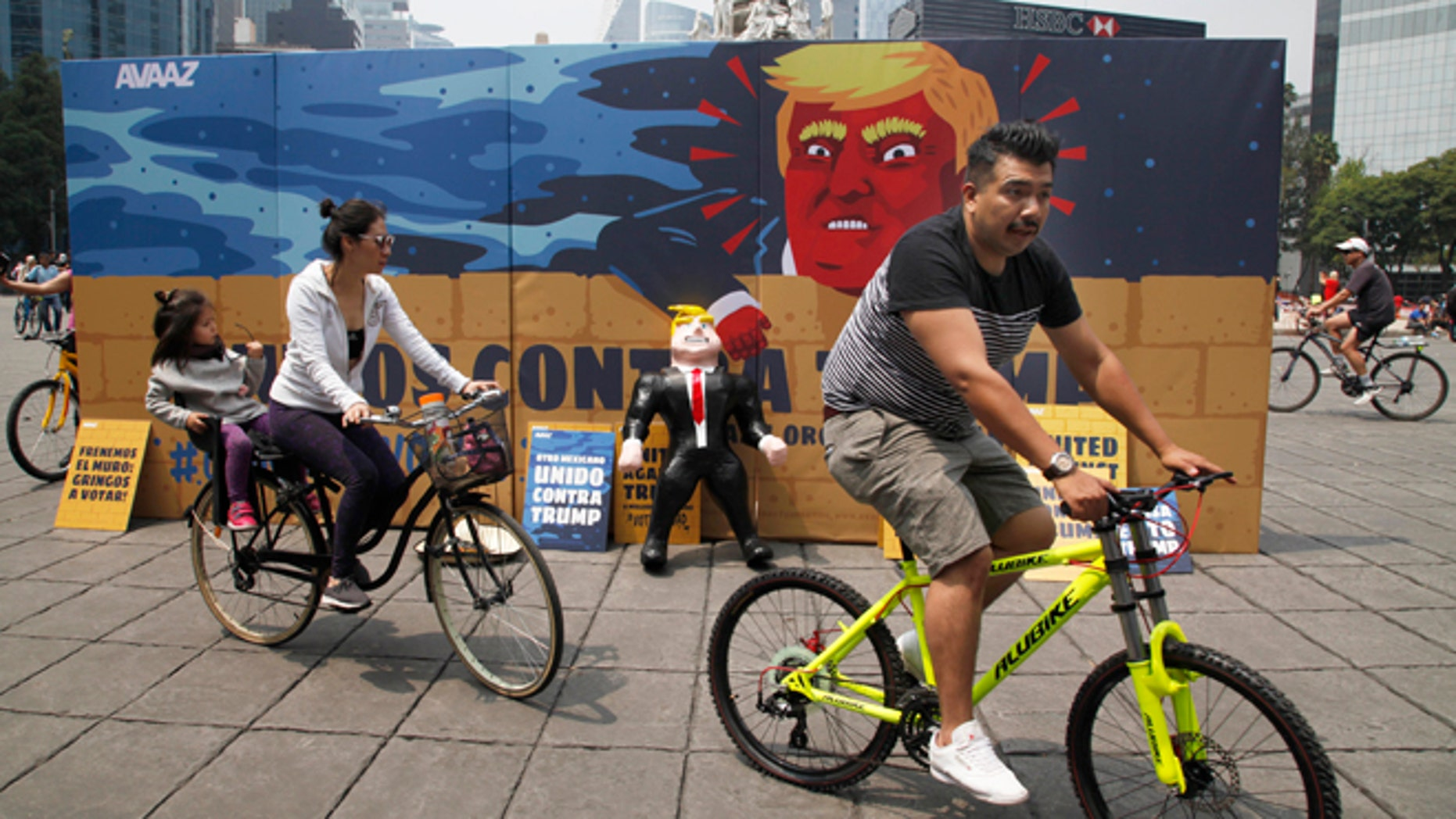 """In this Sunday, Sept. 25, 2016 photo, a family of three ride their bicycles past a piñata depicting U.S. Republican presidential nominee Donald Trump propped against a cardboard mural wall with a message in Spanish that reads; """"United against Trump"""" at the Angel of  Independence monument in Mexico City.  The head of Mexicoâs central bank told the Radio Formula network Friday, Sept. 30, 2016, that a Trump presidency âwould be a hurricane and a particularly intense one if he fulfills what he has been saying in his campaign.â  (AP Photo/Marco Ugarte)"""