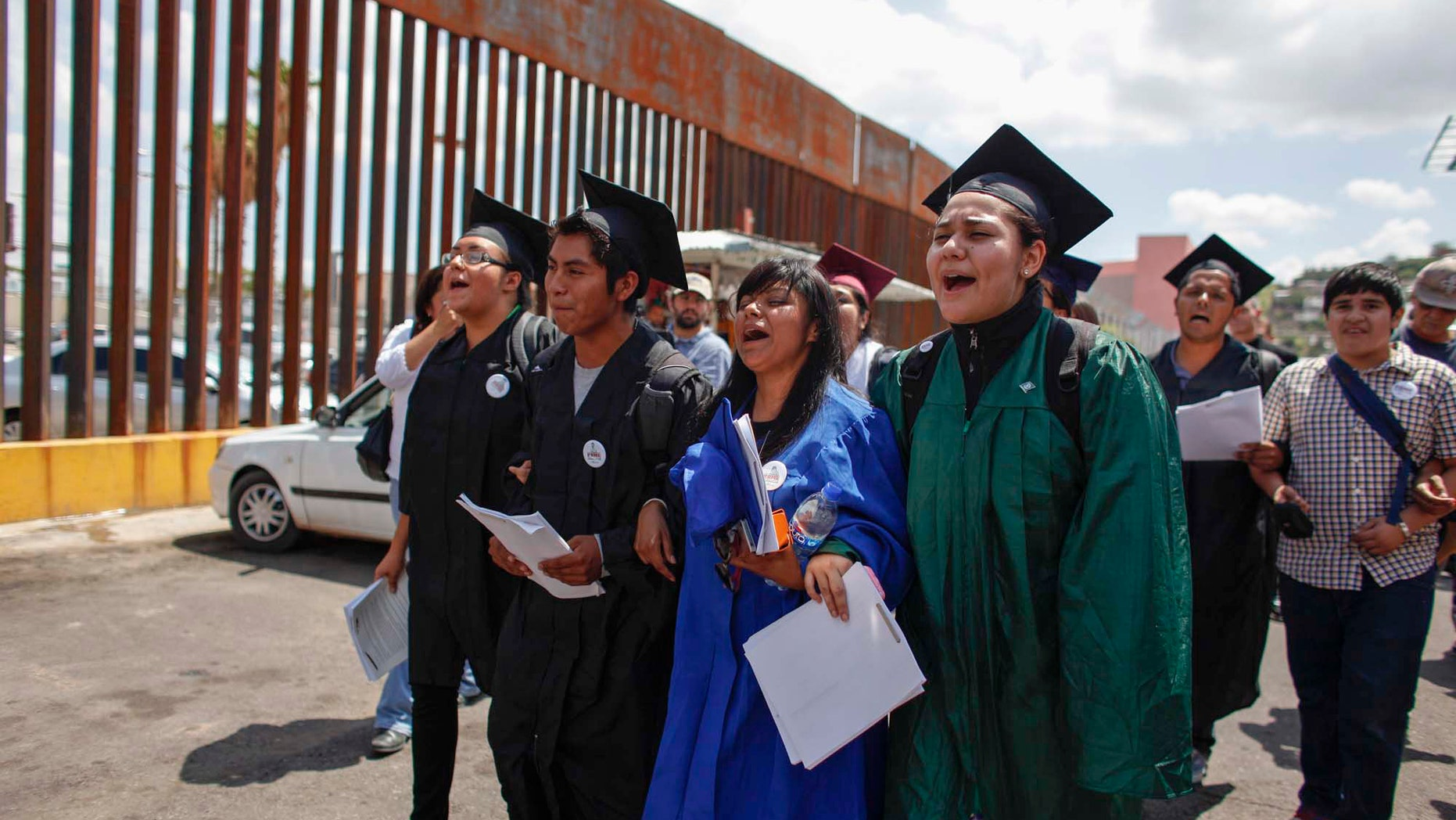 'Dreamers' wearing their school graduation caps and gowns to show their desire to finish school in the U.S., march to the U.S. port of entry in Nogales, Mexico, July 22, 2013.