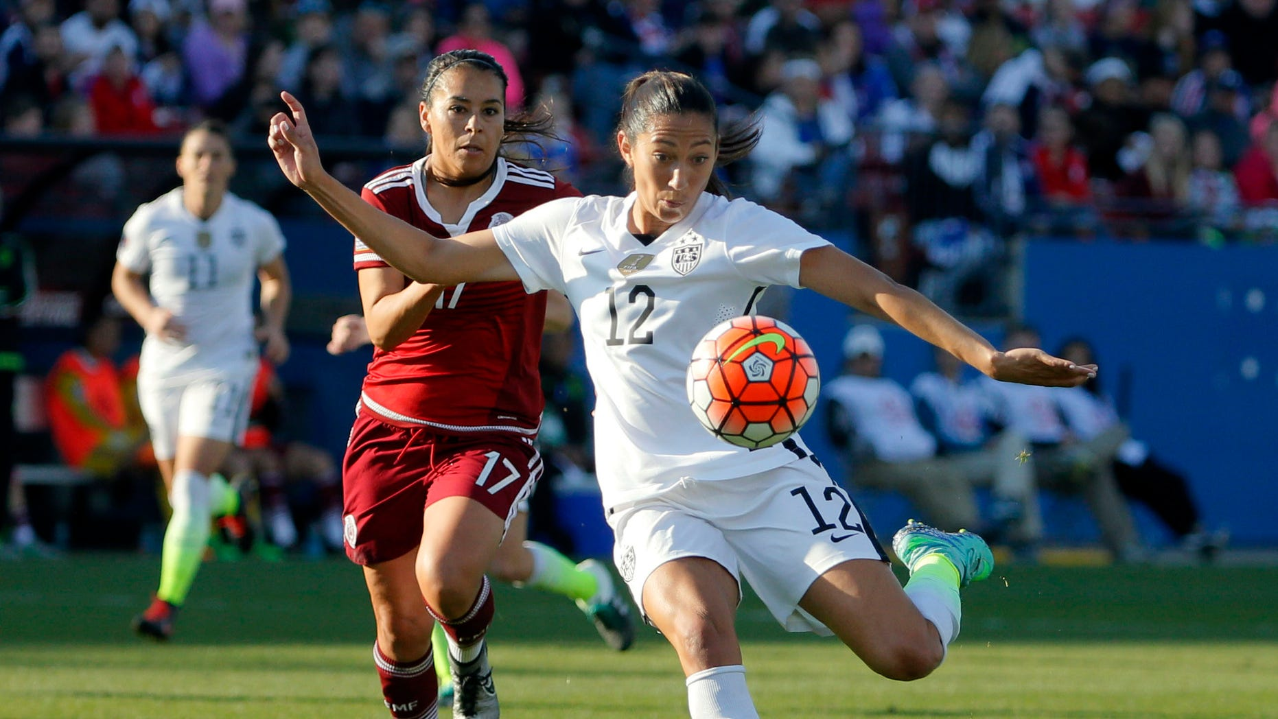 United States forward Christen Press (12) takes a shot at the goal as Mexico midfielder Veronica Perez (17) watches in the second half of a CONCACAF Olympic qualifying tournament soccer match, Saturday, Feb. 13, 2016, in Frisco, Texas. The U.S. won 1-0. (AP Photo/Tony Gutierrez)