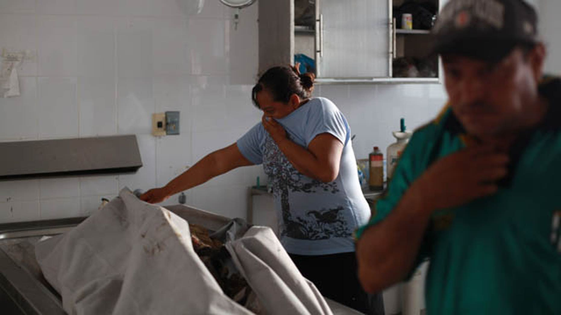 June 18, 2014: Relatives try identify their missing loved ones at the morgue of Cosamaloapan, in Veracruz , Mexico. More than two dozen bodies have been recovered from a mass grave in Veracruz, an eastern Mexican state plagued by attacks on migrants and drug cartel violence, officials said Wednesday. (AP Photo/Felix Marquez)