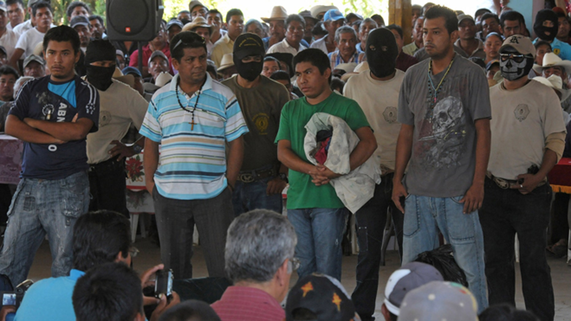 Detained people stand before a community assembly in the town of El Meson, Mexico, Thursday Jan. 31, 2013. Vigilantes who have taken up arms against drug cartel violence and common crime in southern Mexico brought charges ranging from organized crime to kidnapping and extortion against 50 men and three women who they have been holding prisoner at improvised jails, in some cases for weeks. (AP Photo/Bernandino Hernandez)