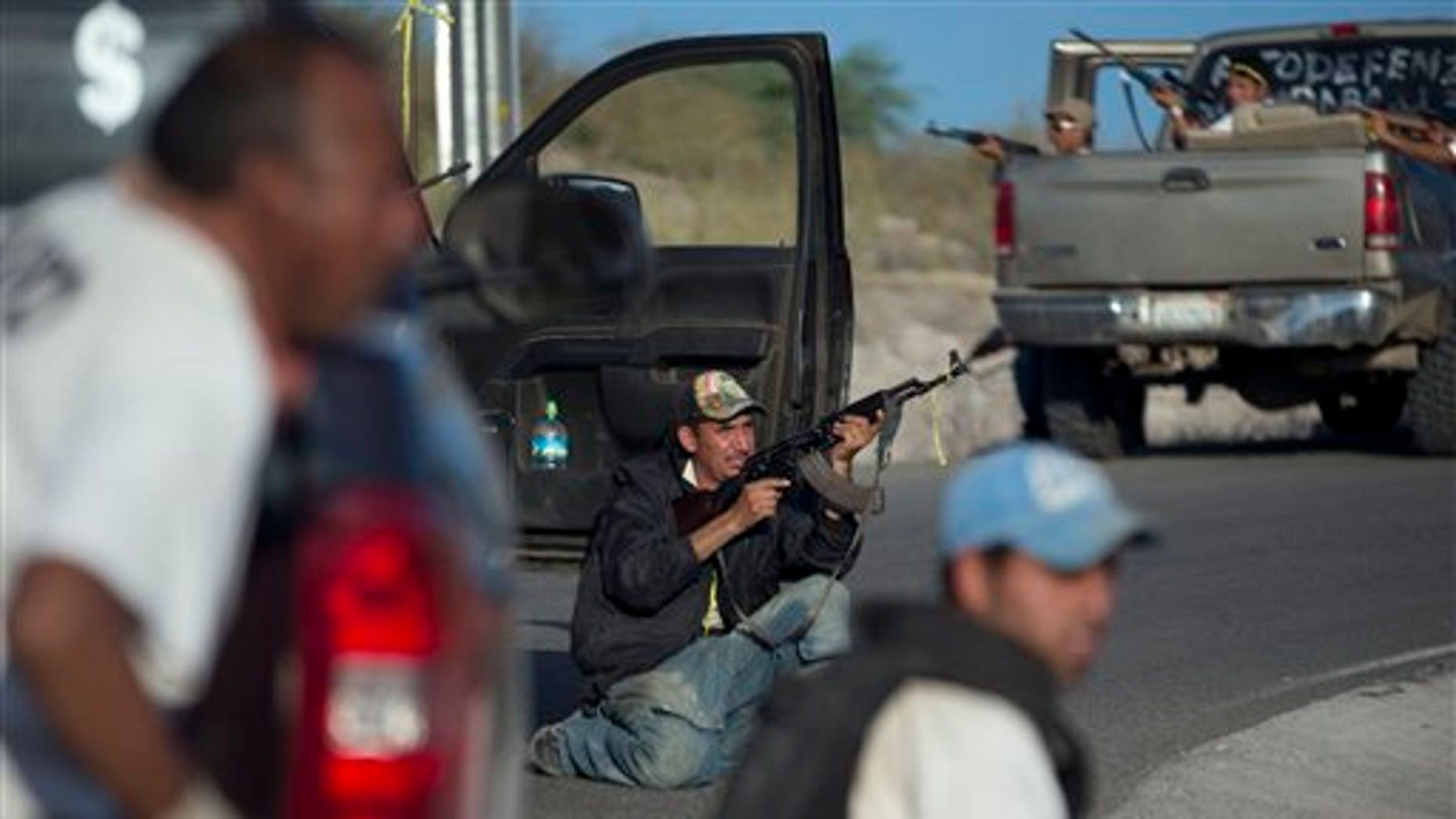 """Member of a self-defense group barricade themselves against possible a possible ambush  as they arrive to the village of Las Yeguas, Michoacan state, Mexico, Saturday, Jan. 11, 2014. Residents from various towns in Michoacan are protesting the arrival of vigilantes, or members of """"self-defense"""" groups, to their communities. Vigilante groups have formed to confront drug cartels in parts of Michoacan. The Knights Templar ( Los Templarios ), a quasi-religious drug cartel, controls the area and most of the state.(AP Photo/Eduardo Verdugo)"""