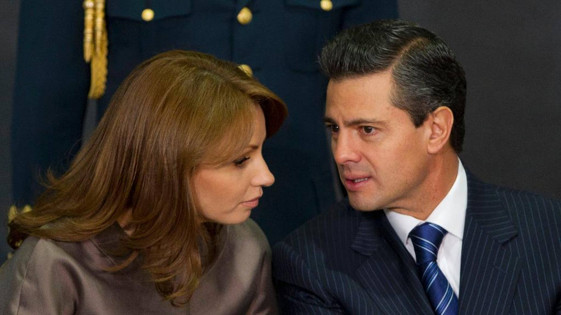"""March 13, 2013: In this file photo, Mexico's President Enrique Pena Nieto, right, speaks to his wife Angelica Rivera as they attend a ceremony launching the program """"Life insurance for female heads of family"""" at Los Pinos presidential residence in Mexico City. (AP)"""