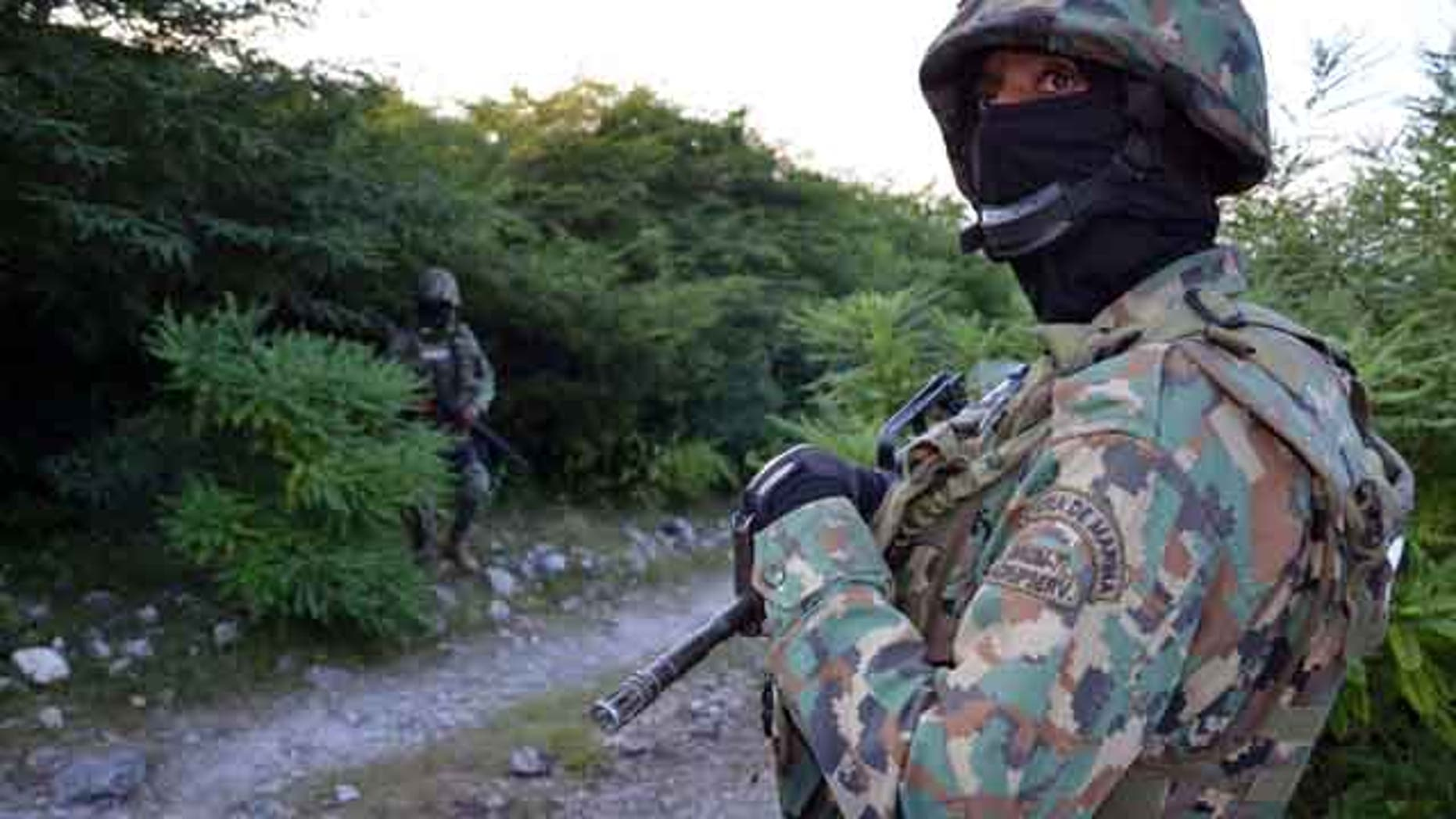 October 27, 2014: Mexican marines guard the area where new clandestine mass graves were found near the outskirts of Cocula, Mexico. (AP Photo/Alejandrino Gonzalez)