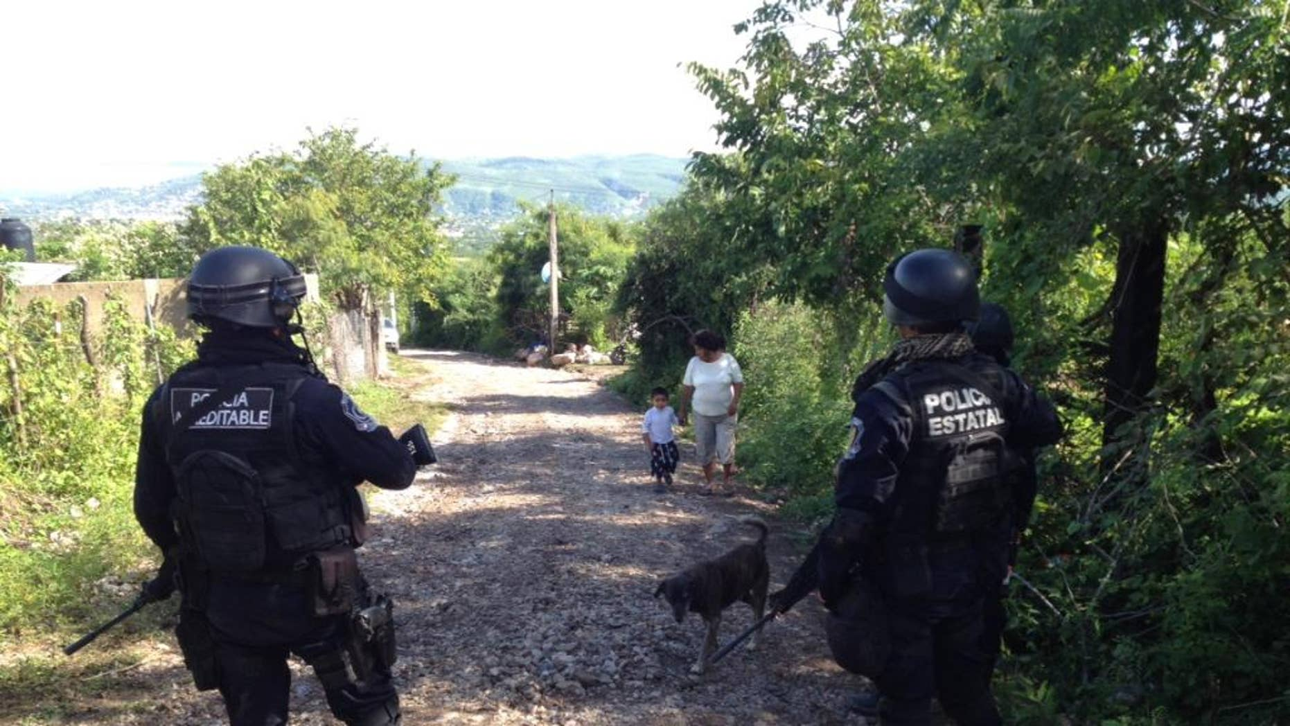 State police guard the road leading to the site where an alleged clandestine grave was found near the town of Pueblo Viejo, Mexico, Saturday, Oct. 4,2014. The clandestine grave holding an undetermined number of bodies was found outside a town where violence last weekend resulted in six deaths and the disappearance of 43 students, Mexican officials said Saturday. (AP Photo/Alejandrino Gonzalez)