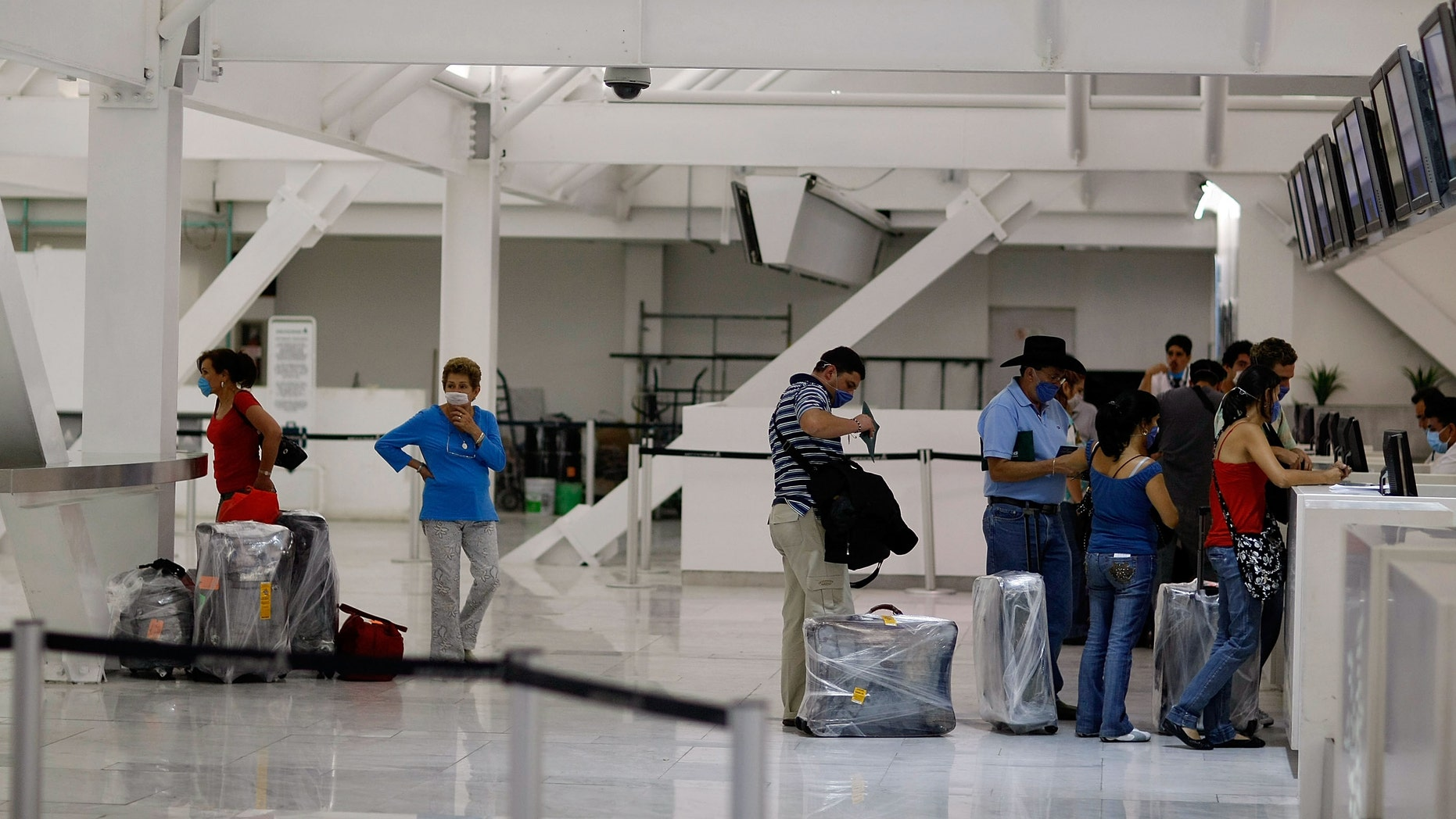 """MEXICO CITY - APRIL 29:  People wear surgical masks to help prevent contracting the swine flu as they check in for the Mexicana airlines flight at the Mexico City International Airport on April 29, 2009 in Mexico City, Mexico. Cases of swine flu, the strain known as H1N1 virus, have been confirmed in nine countries, including Mexico, where at least 2,400 are believed to be infected, with the number of deaths attributed to the virus believed to be more than 150. The World Health Organization today raised the threat level to """"phase 5,"""" indicating a """"pandemic is imminent.""""  (Photo by Joe Raedle/Getty Images)"""