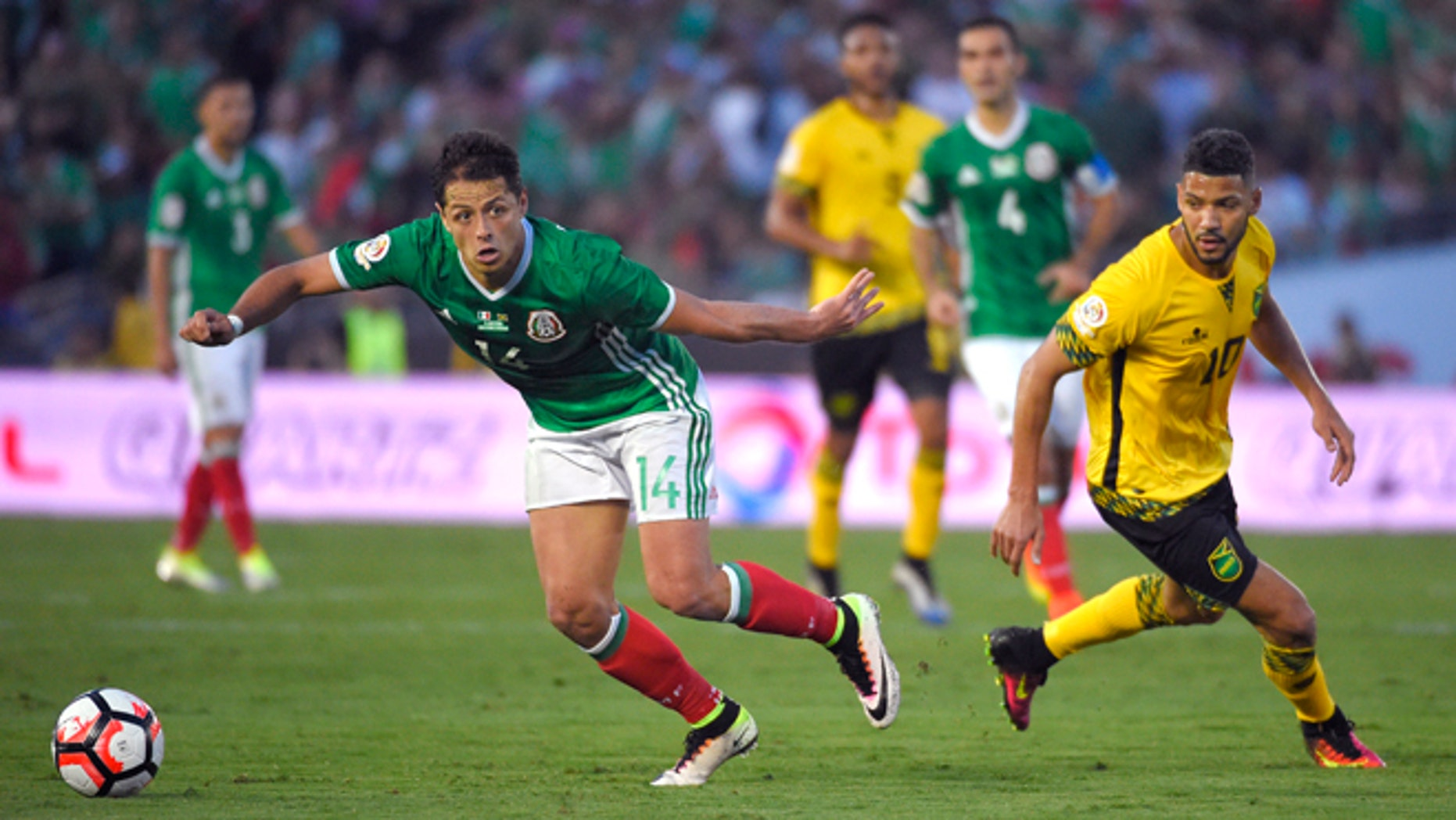 Mexico forward Chicharito, left, moves the ball as Jamaica midfielder Joel McAnuff pressures him during a Copa America group C soccer match at the Rose Bowl, Thursday, June 9, 2016, in Pasadena, Calif. (AP Photo/Mark J. Terrill)