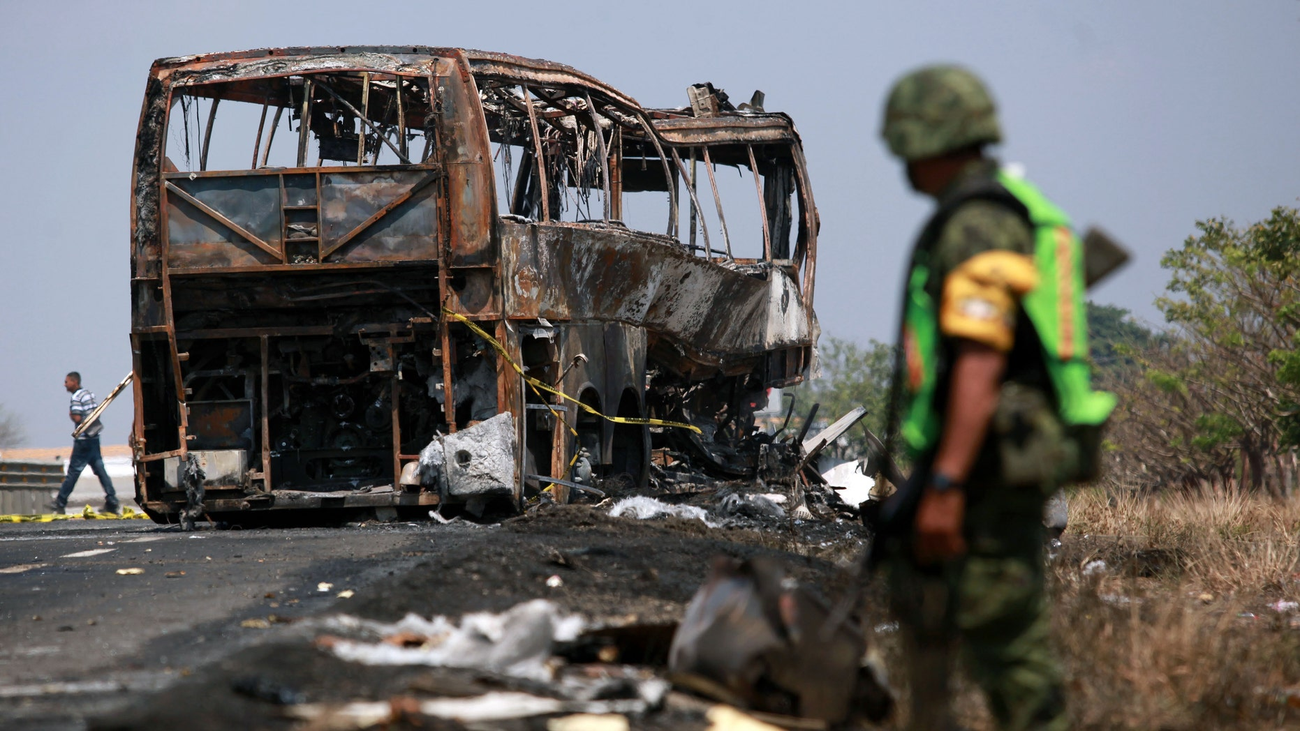 A soldier guards the site where a passenger bus slammed into a broken-down truck and burst into flames near the town of Ciudad Isla in the Gulf state of Veracruz, Mexico, Sunday, April 13, 2014. Dozens of people traveling on the bus to Mexico City burned to death inside the bus. (AP Photo/Felix Marquez)