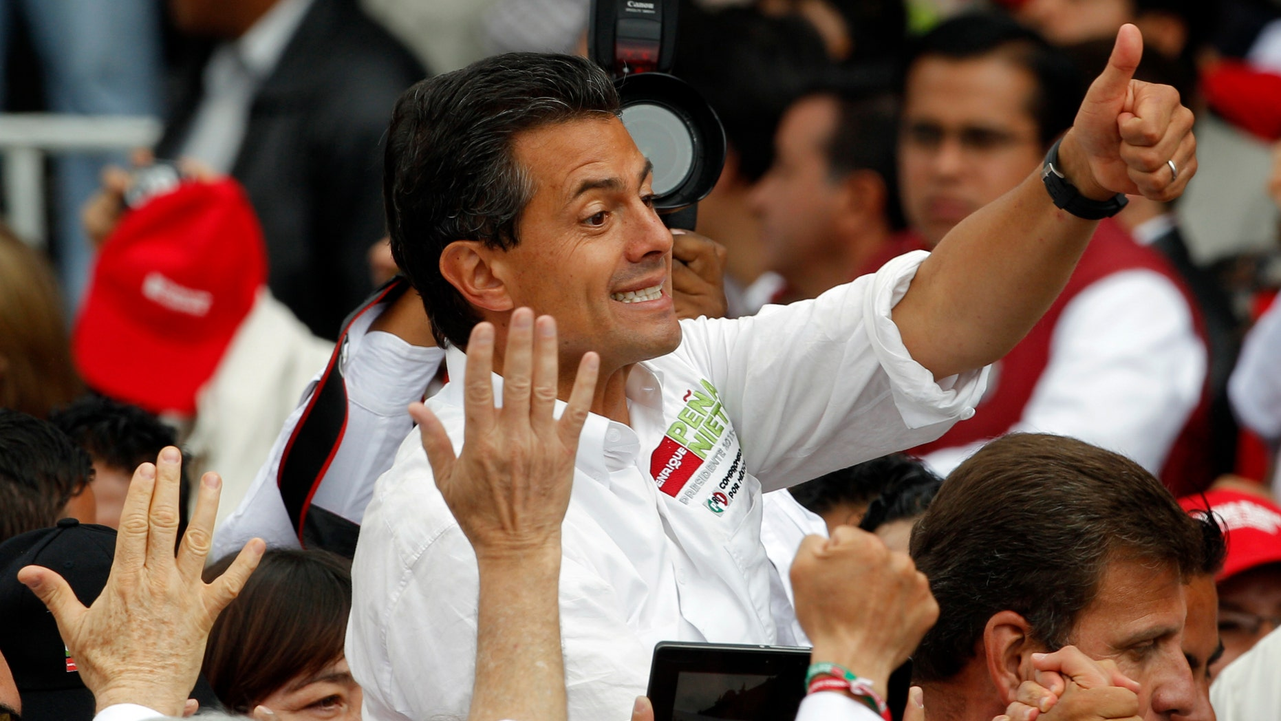Presidential candidate Enrique Peña Nieto of the Institutional Revolutionary Party (PRI), flashes a thumbs up to supporters during his closing campaign rally in Toluca, Mexico, on Wednesday. (AP Photo/Andres Leighton)