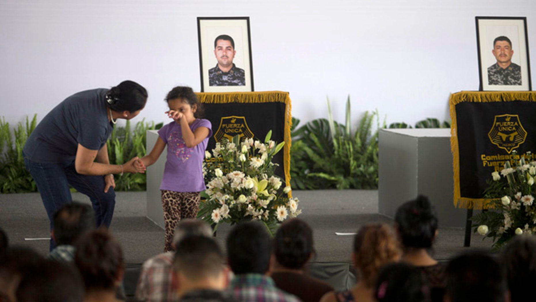 A girl weeps during a ceremony to honor slain policemen in Tlaquepaque, Mexico, Wednesday, April 8, 2015.