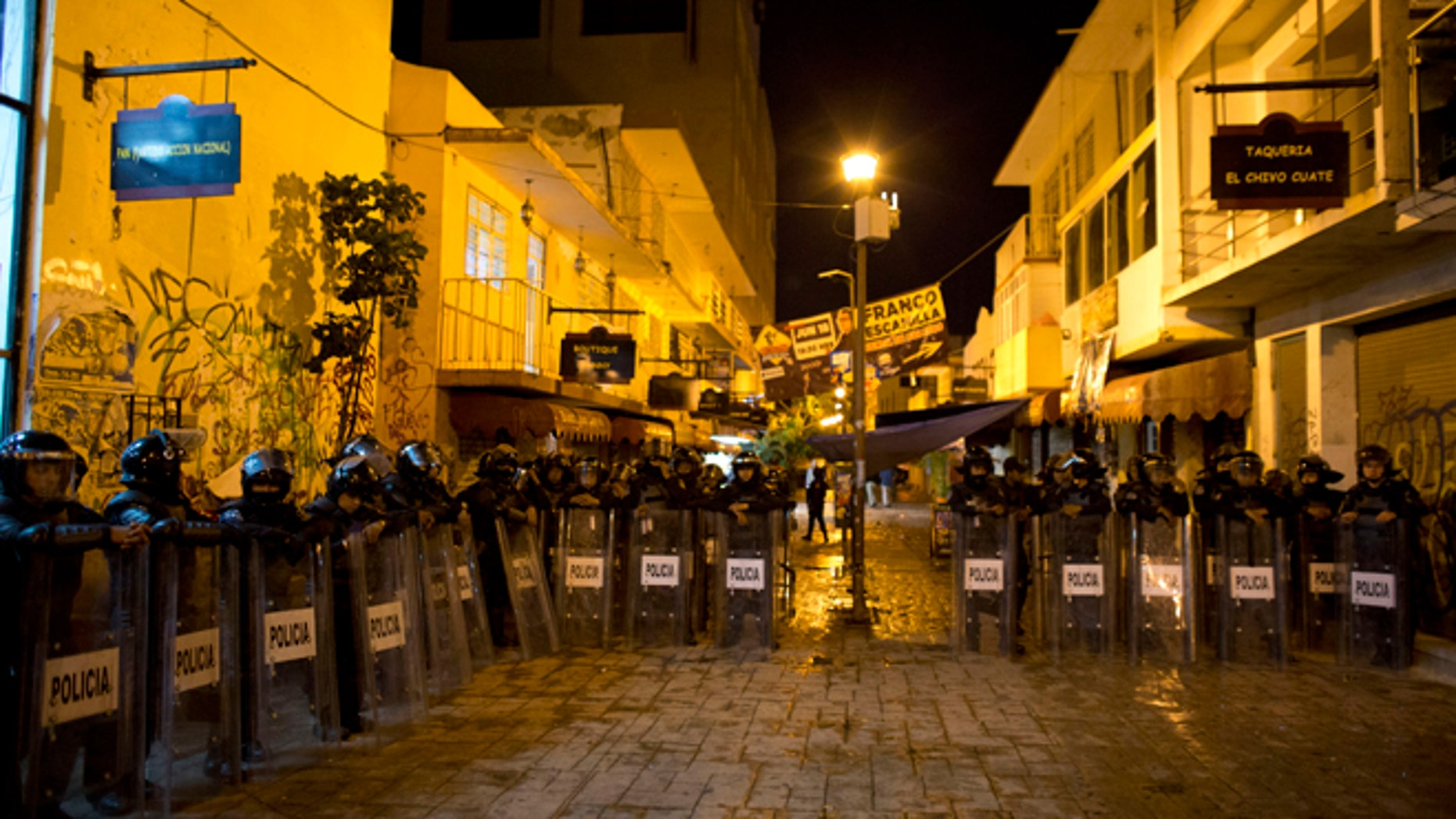 Police stand guard in the pedestrian street where a small explosive was tossed at National Action Party headquarters, in Chilpancingo, Mexico, in the early morning hours of Friday, June 5, 2015. Radical groups and unionized teachers have vowed to block Sunday's voting for the lower house of congress, nine governorships and hundreds of mayorships. (AP Photo/Rebecca Blackwell)