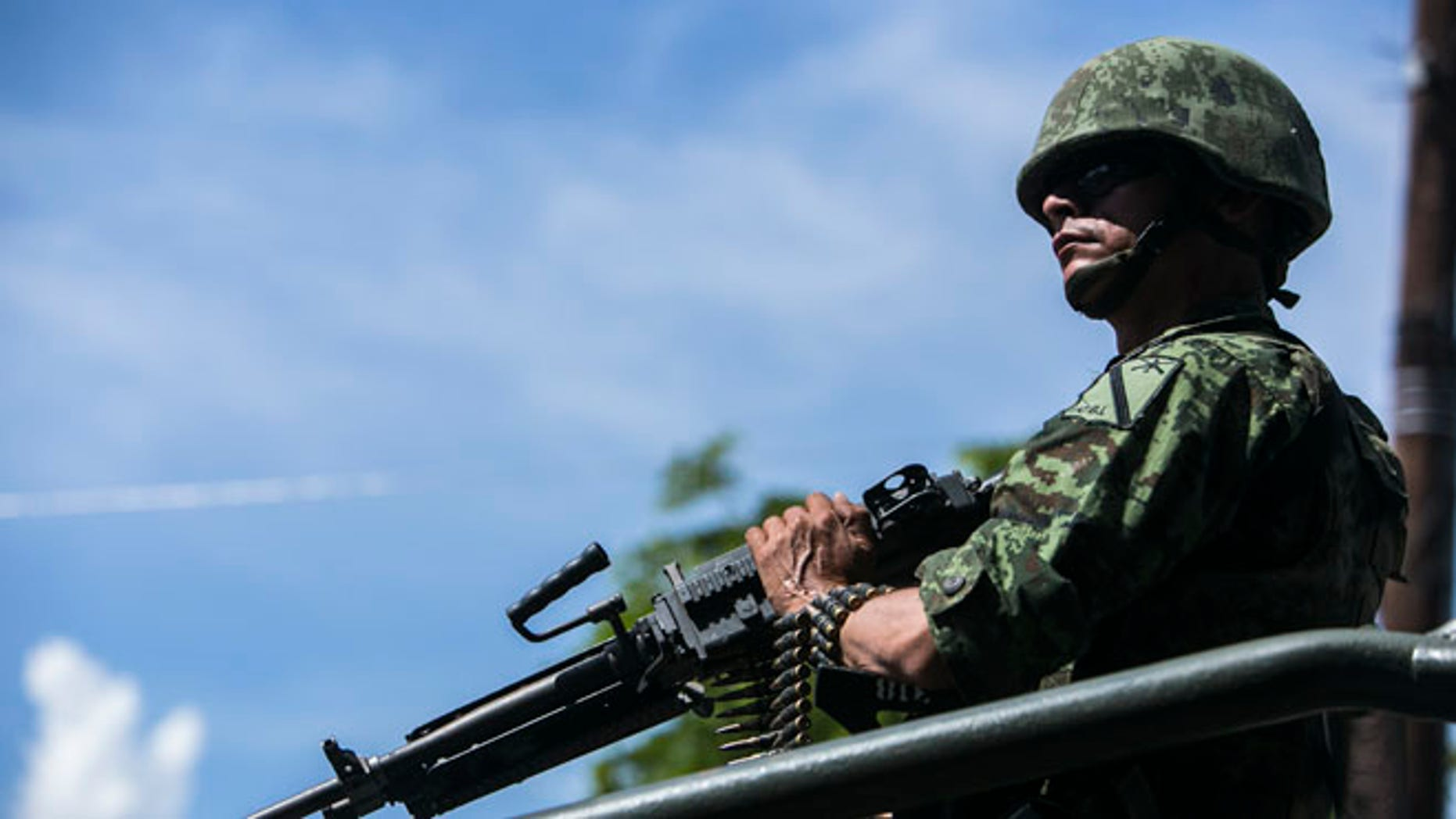 A soldier rides atop a military vehicle in a convoy carrying the bodies of soldiers killed one day earlier in an ambush, inside the Novena Military Zone in Culiacan, Sinaloa State, Mexico, Saturday, Oct. 1, 2016. A brazen ambush on a military convoy Friday left five soldiers dead and 10 wounded in what was the worst attack on military personnel since 2015, when drug cartel gunmen in the state of Jalisco shot down an army helicopter with a rocket launcher, killing 10 people.(AP Photo/Rashide Frias)