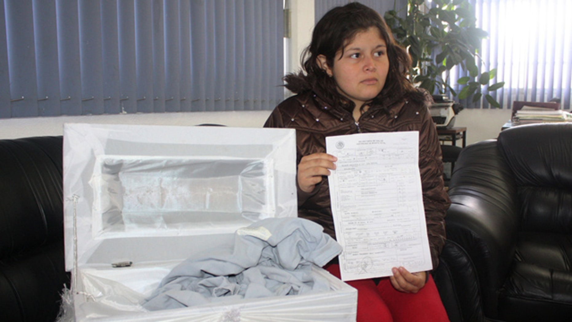August 5: Dafne Hernandez, shows a death certificate of her newborn daughter and a coffin meant to be used at her burial during an interview with local media in Tulancingo, Mexico. (AP)