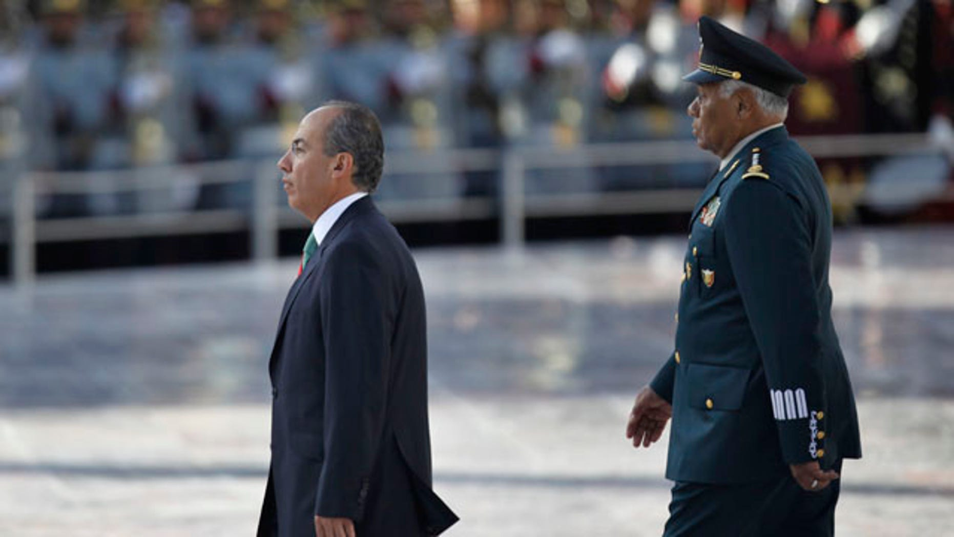 """September 13: Mexico's President Felipe Calderon, walks along Mexico's Defense Secretary Guillermo Galvan during the anniversary of the battle of the """"Ninos Heroes"""", or Heroic Childre in Mexico City.  The """"Ninos Heroes"""", or Heroic Children were a group of young cadets who died defending the military academy in Mexico City during the Mexican-American war in 1847. (AP)"""