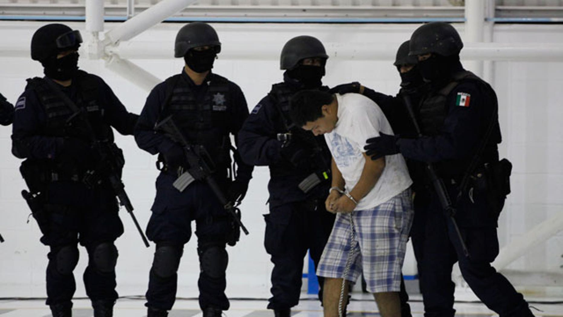 Federal police present an alleged drug cartel member to the press in Mexico City, Friday Aug. 13, 2010. Five alleged members of La Linea drug cartel, accused of participating in the killings of two federal police officers, were arrested Thursday in the border town of Ciudad Juarez, according to the police.