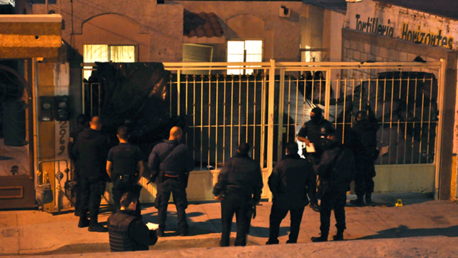 Oct. 22, 2010: Mexican federal police officers stand outside a home after the exterior gate was covered with a plastic tarp in the northern city of Ciudad Juarez, Mexico. At least 13 people were shot dead and 15 wounded in an attack on this house during a party in Ciudad Juarez, the second such massacre in less than a week in the violent border city.