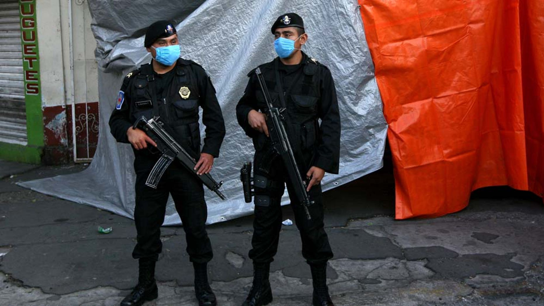 Mexico City police guard a refrigerated truck carrying bodies that were found in mass graves in northern Mexico, after it arrived in Mexico City, Thursday April 14, 2011. Mexican investigators found a clandestine grave with six bodies in Tamaulipas state, bringing to 122 the number of bodies found in pits in a region near the U.S. border that is wracked by battling drug cartels, authorities said Wednesday. (AP Photo/Marco Ugarte)