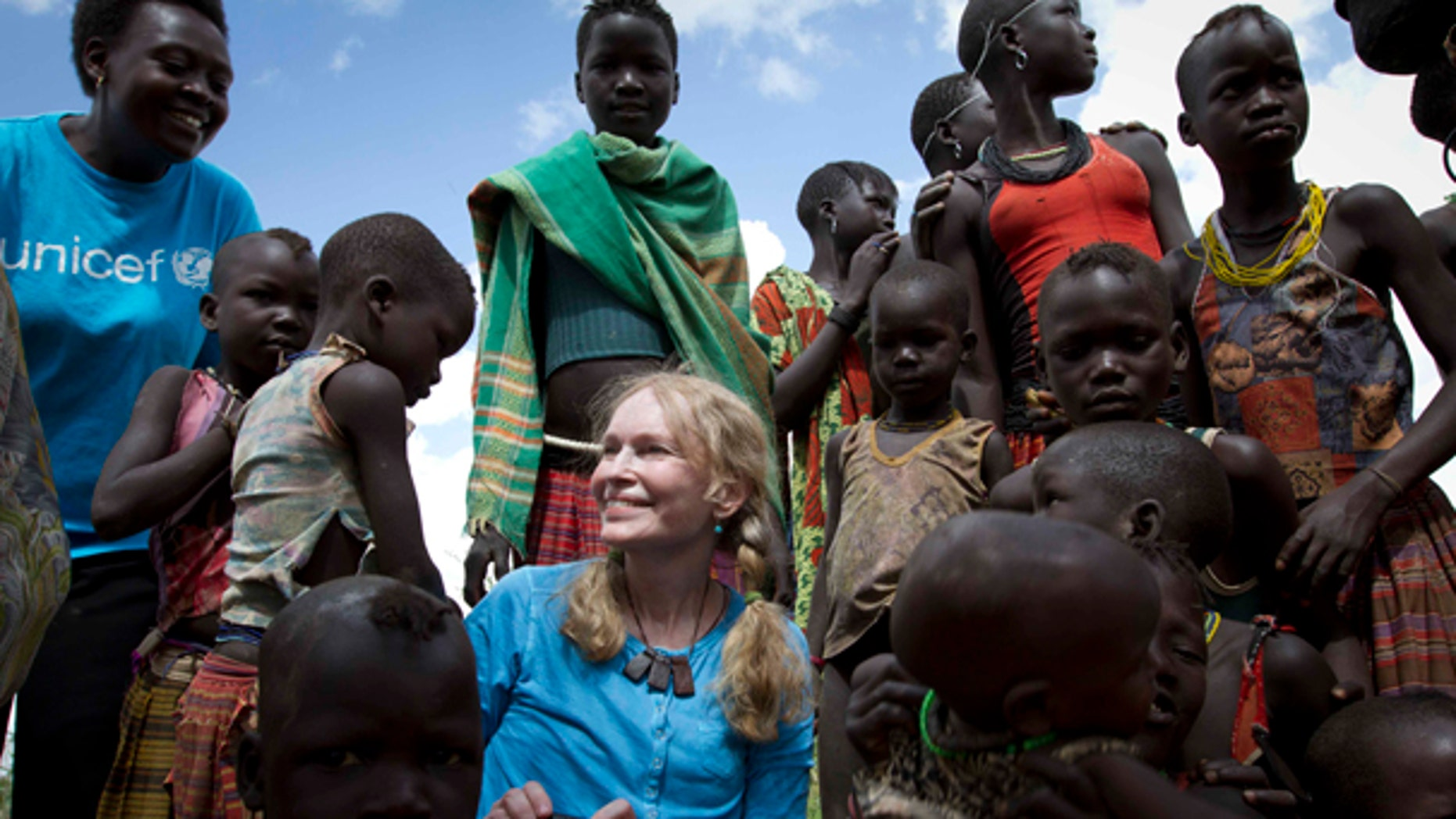 July 15: UNICEF Goodwill Ambassador, US actress Mia Farrow with a group of Karimojong children at a Tokul near the town of Kitodo, in the far north west of Uganda. (AP)
