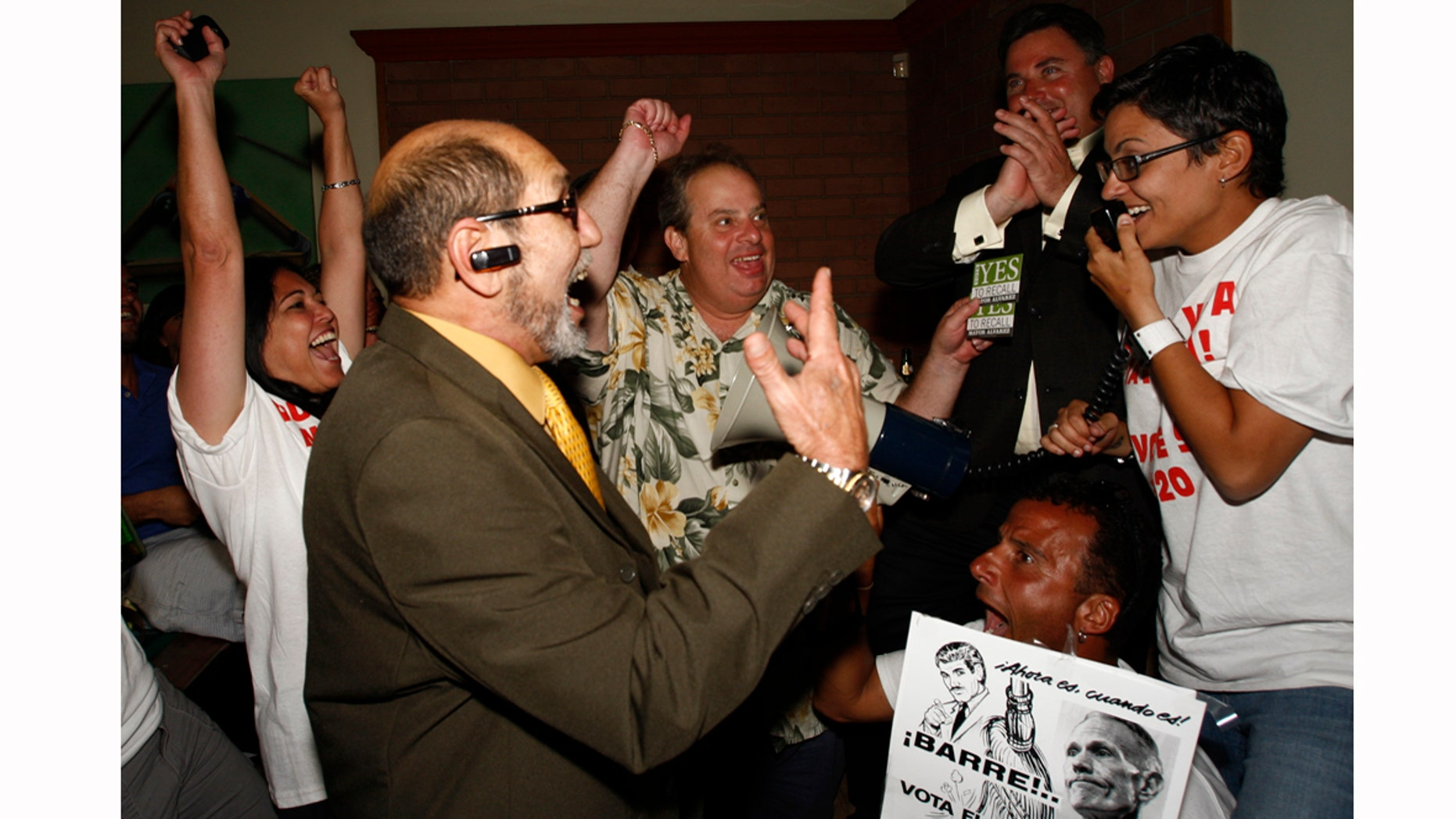 Members of Miami Voice and Miami Lakes Mayor Michael Pizzi, join Mimi Planas, left, Ernesto Lopez, Kevin Moejon, Ernesto Hernandez, holding the sign, Vanessa Brito, right, as they celebrate the results recalling County Commissioner Natacha Seijas and Miami Mayor Carlos Alvarez on Tuesday, March 15, 2011, inside the Billiard Club in Miami Lakes, Fla. (AP Photo/The Miami Herald, Carl Juste) MAGS OUT
