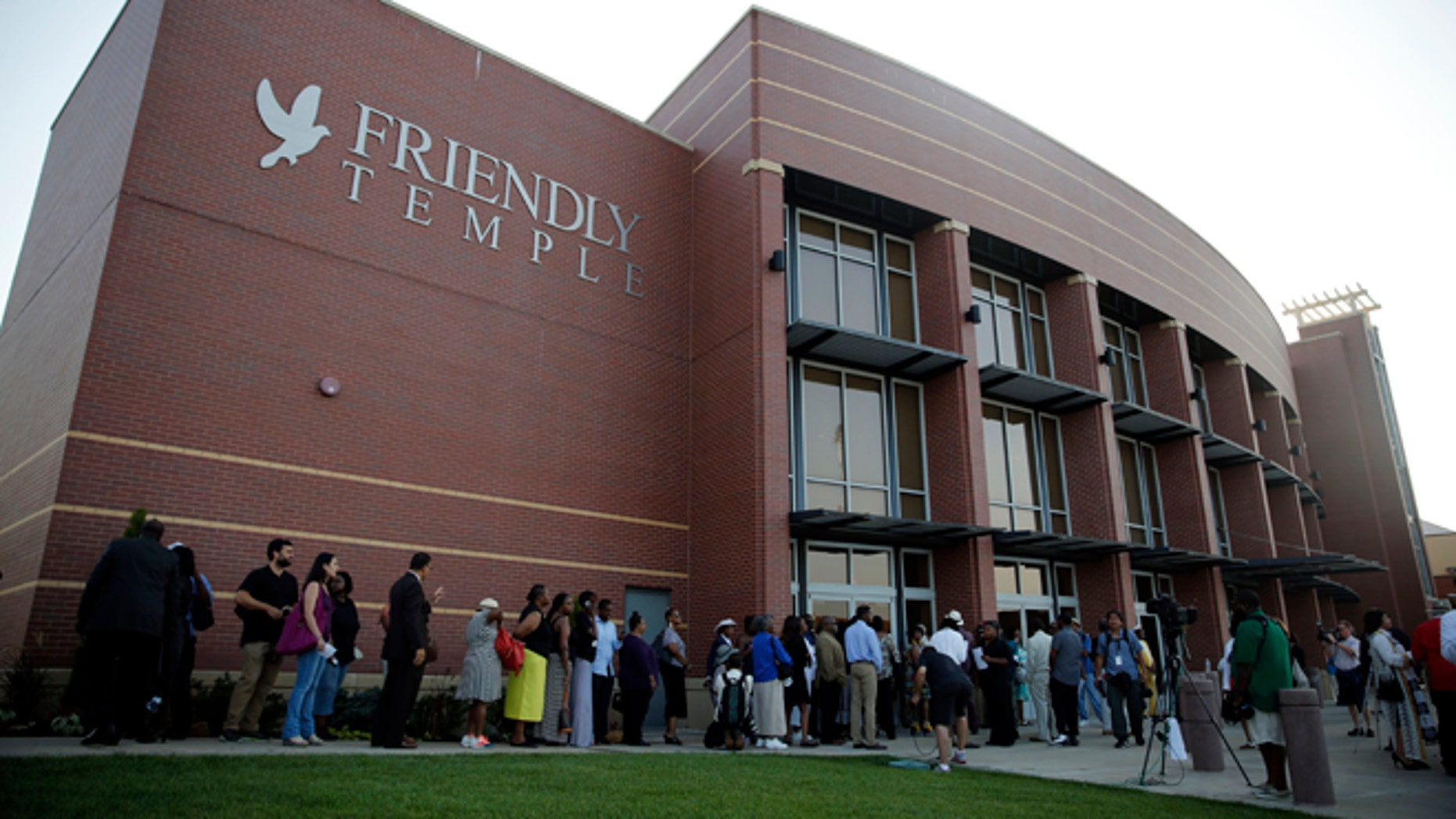 People begin to line up to attend the funeral for Michael Brown, Monday, Aug. 25, 2014, in St. Louis.