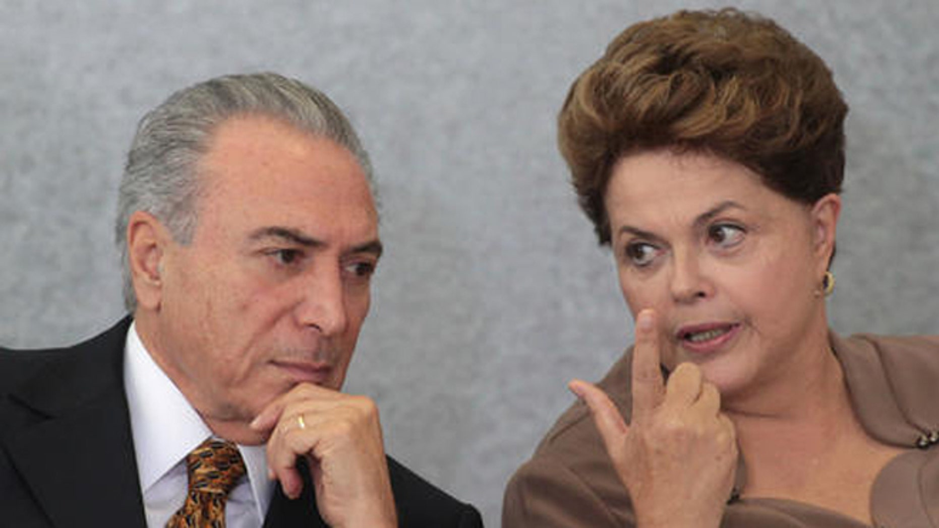 FILE - In this April 24, 2012 file photo, Brazil's President Dilma Rousseff, right, talks with Vice President Michel Temer, during a ceremony at Planalto Palace in Brasilia, Brazil. Three ministers in the government of interim President Temer, who took over when Rousseff was suspended in May, were forced to resign right after taking office because of corruption allegations. And Temer himself has been fingered for bribery by witnesses in the Petrobras investigation who have reached plea deals with prosecutors, though so far he has not been charged. (AP Photo/Eraldo Peres)