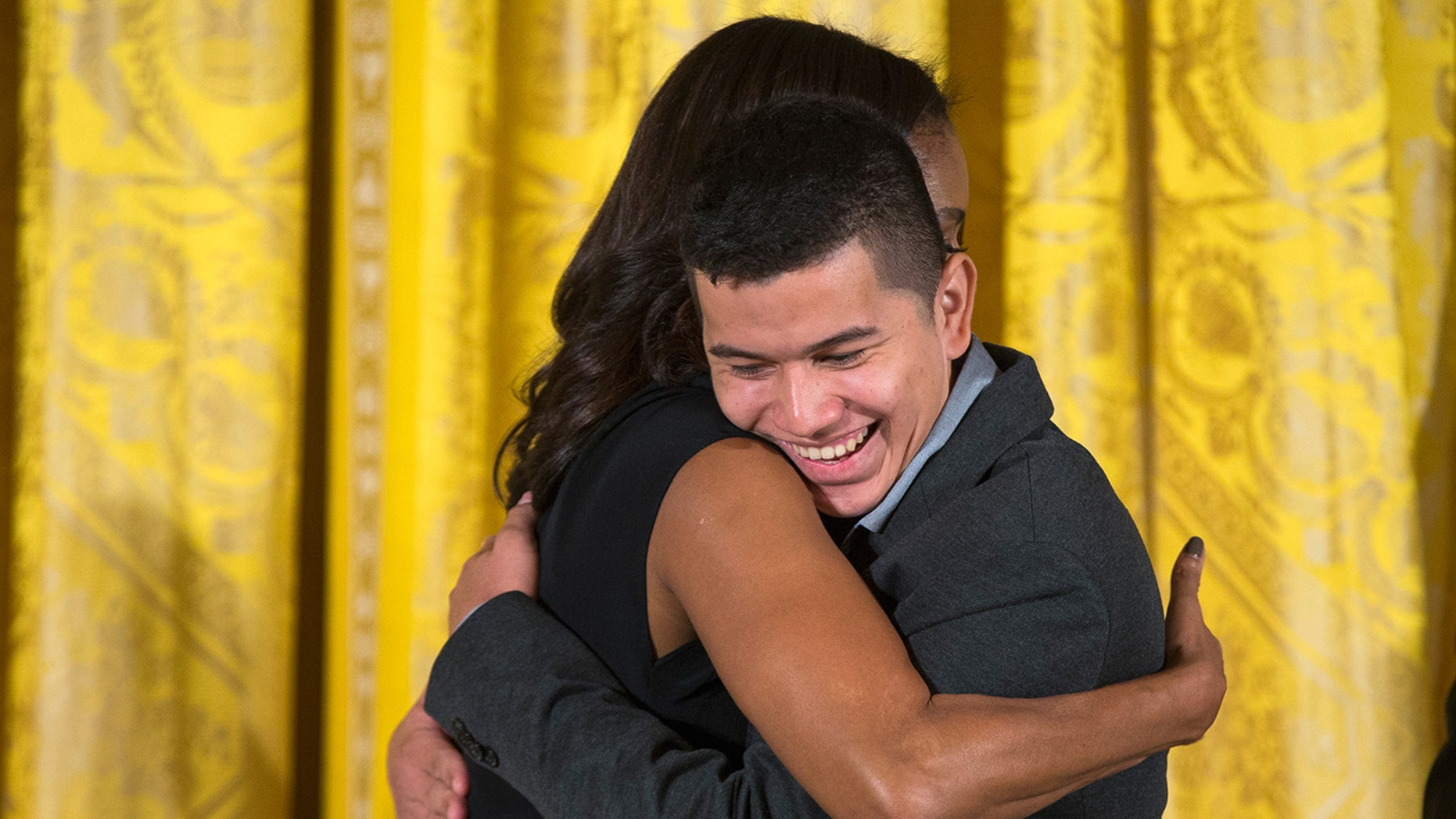 First lady Michelle Obama hugs Jefry Amaya of the Organization for Youth Empowerment in El Progreso, Honduras.