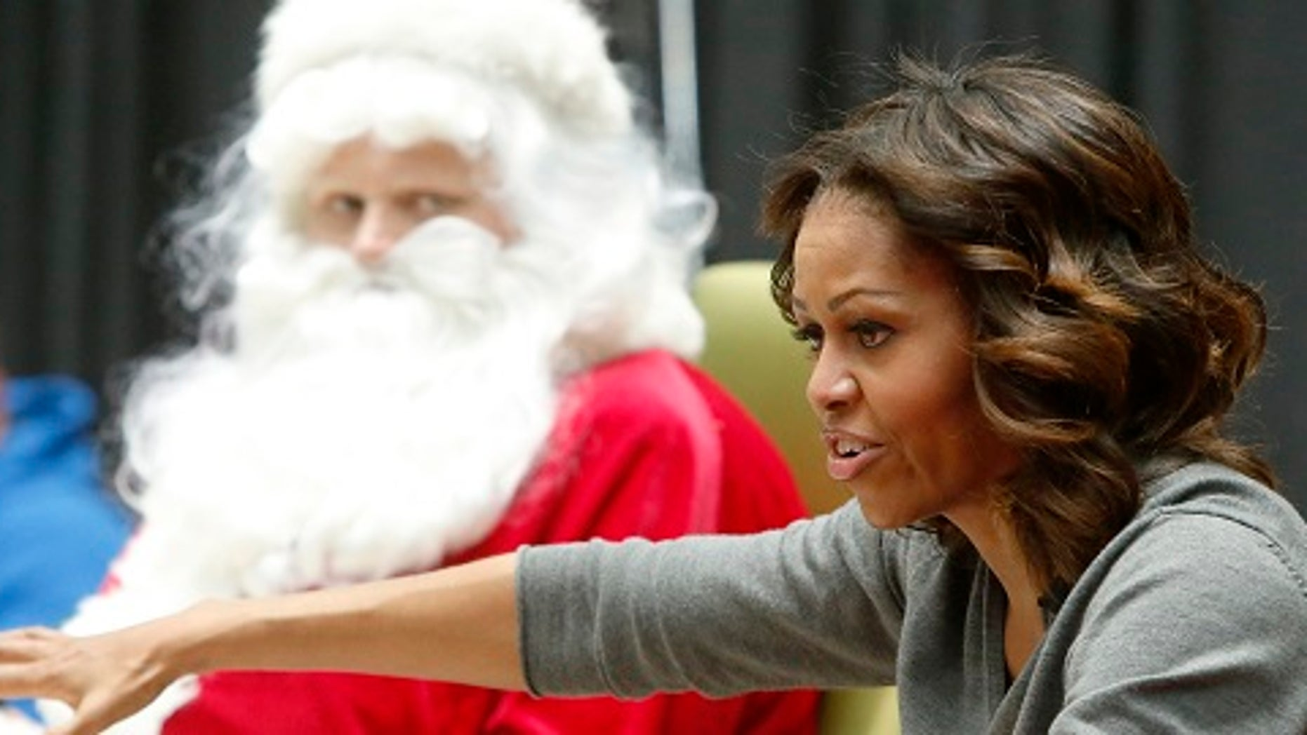 """U.S. first lady Michelle Obama visits young patients and their families at the Children's National Medical Center in Washington, December 16, 2013. Obama read the book """"'Twas the Night Before Christmas"""" before greeting the children along with Santa Claus and presidential dogs Sunny and Bo.  REUTERS/Jonathan Ernst    (UNITED STATES - Tags: POLITICS HEALTH ENTERTAINMENT SOCIETY) - RTX16LGE"""