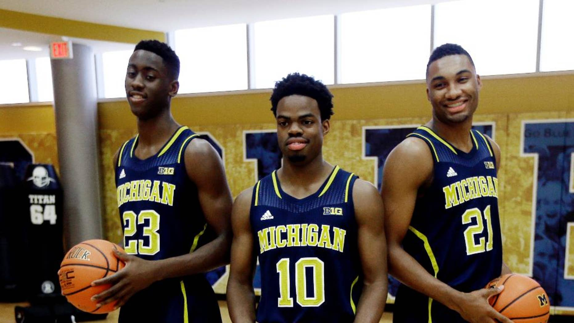 Michigan guard Caris Levert (23), Derrick Walton Jr., (10) and Zak Irvin (21) pose during the men's NCAA college basketball media day in Ann Arbor, Mich., Thursday, Oct. 30, 2014. (AP Photo/Carlos Osorio)