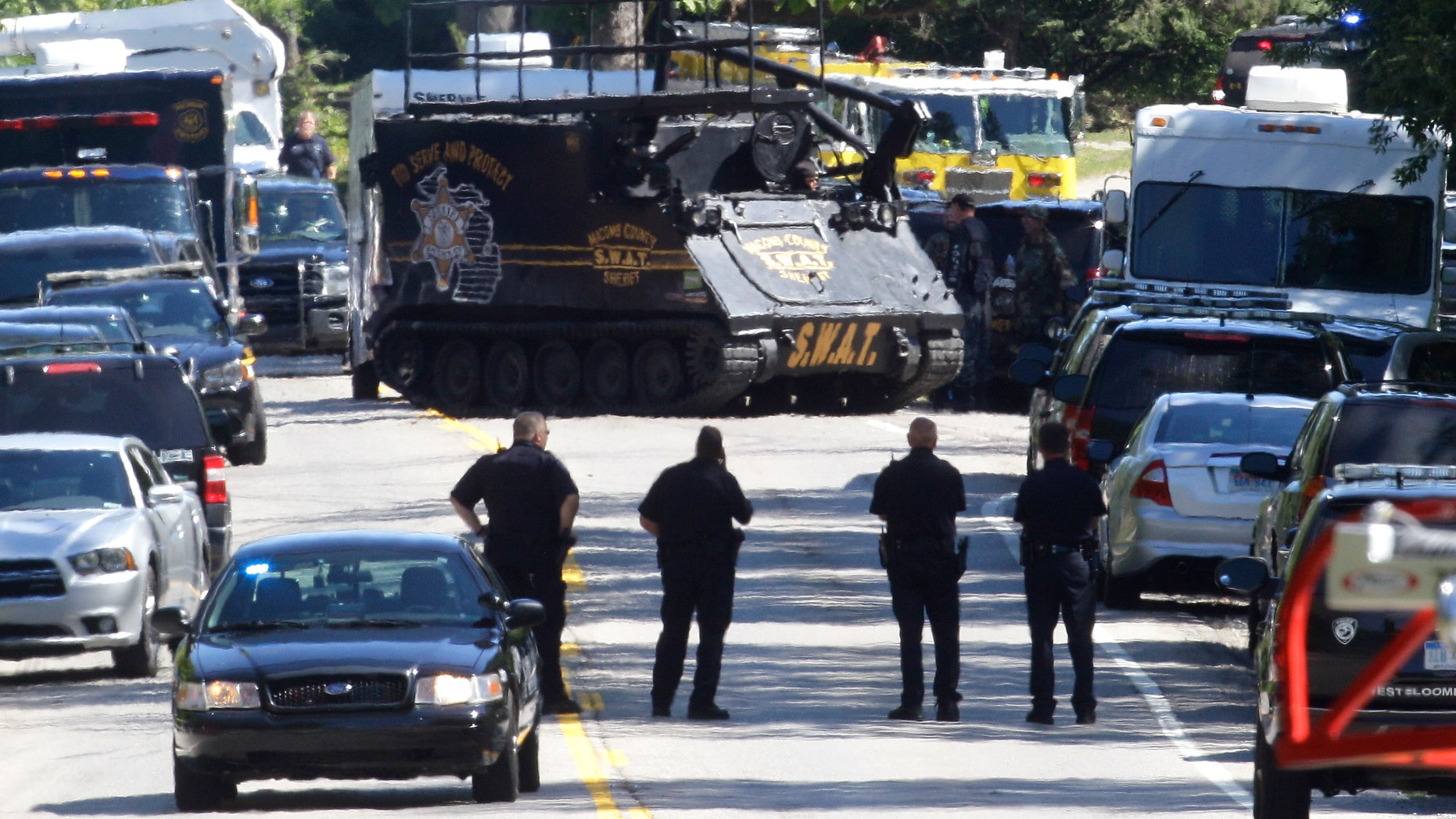 Sept. 10, 2012: An armored vehicle advances on a house where they believe a man suspected in the fatal shooting of a police officer had barricaded himself inside in West Bloomfield, Mich.