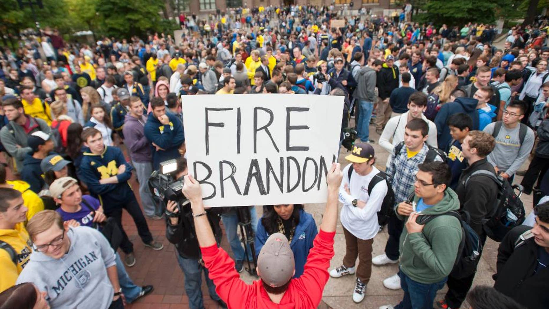 """In a Sept. 30, 2014 photo, law student Edward Mears holds a """"Fire Brandon"""" sign during a protest on the campus of the University of Michigan over the recent football game against Minnesota where quarterback Shane Morris was left in the game after receiving a concussion. About 1,000 University of Michigan students marched to the home of school President Mark Schlissel to protest against the performance of athletic director Dave Brandon and football coach Brady Hoke.  (AP Photo/The Detroit News, David Guralnick)"""