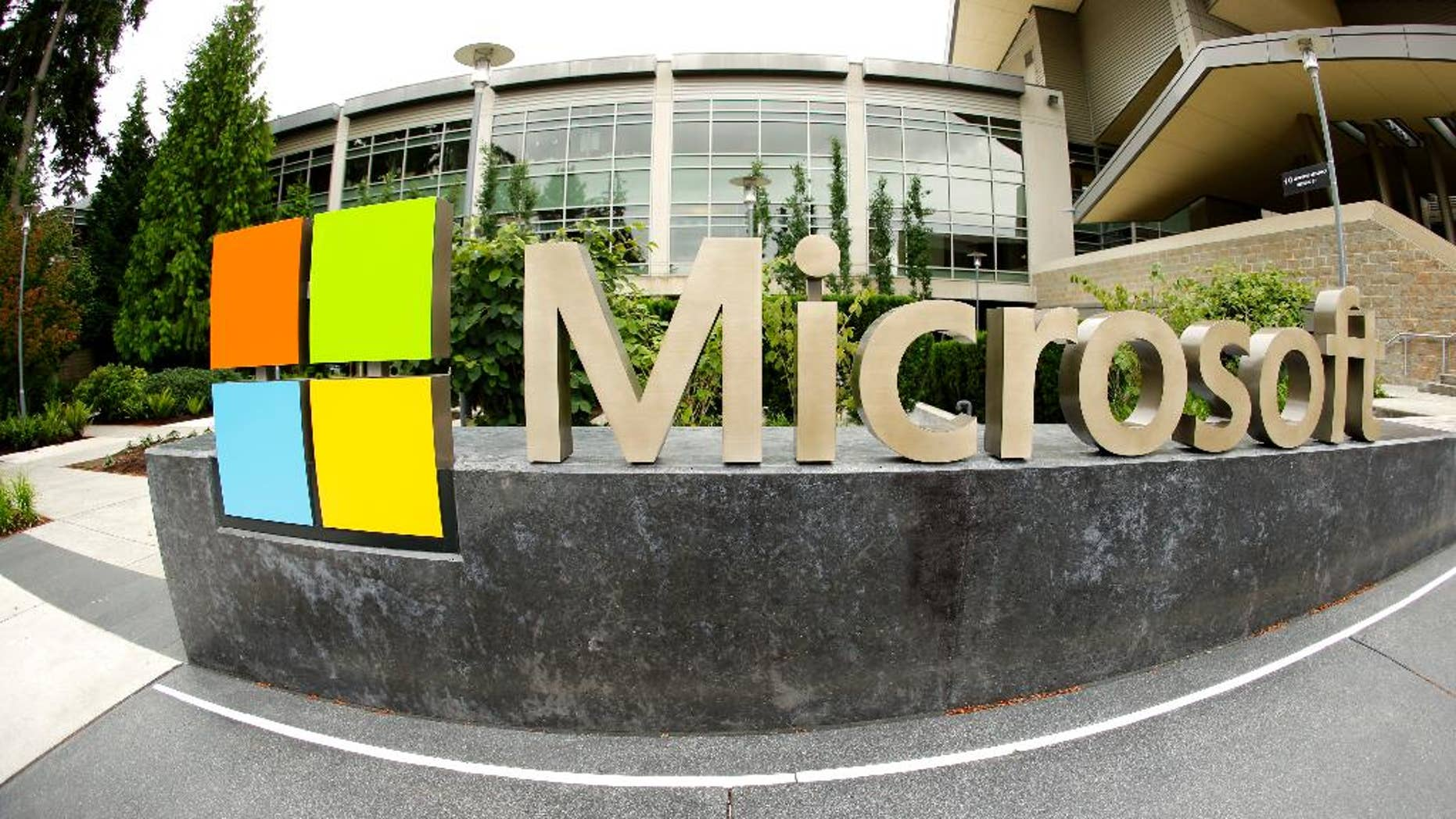 FILE - This July 3, 2014 file photo taken with a fisheye lens shows Microsoft Corp. signage outside the Microsoft Visitor Center in Redmond, Wash. Microsoft will acquire Stockholm-based game maker Mojang, the maker of the popular game Minecraft for $2.5 billion, the company announced Monday, Sept. 15, 2014. (AP Photo Ted S. Warren, File)