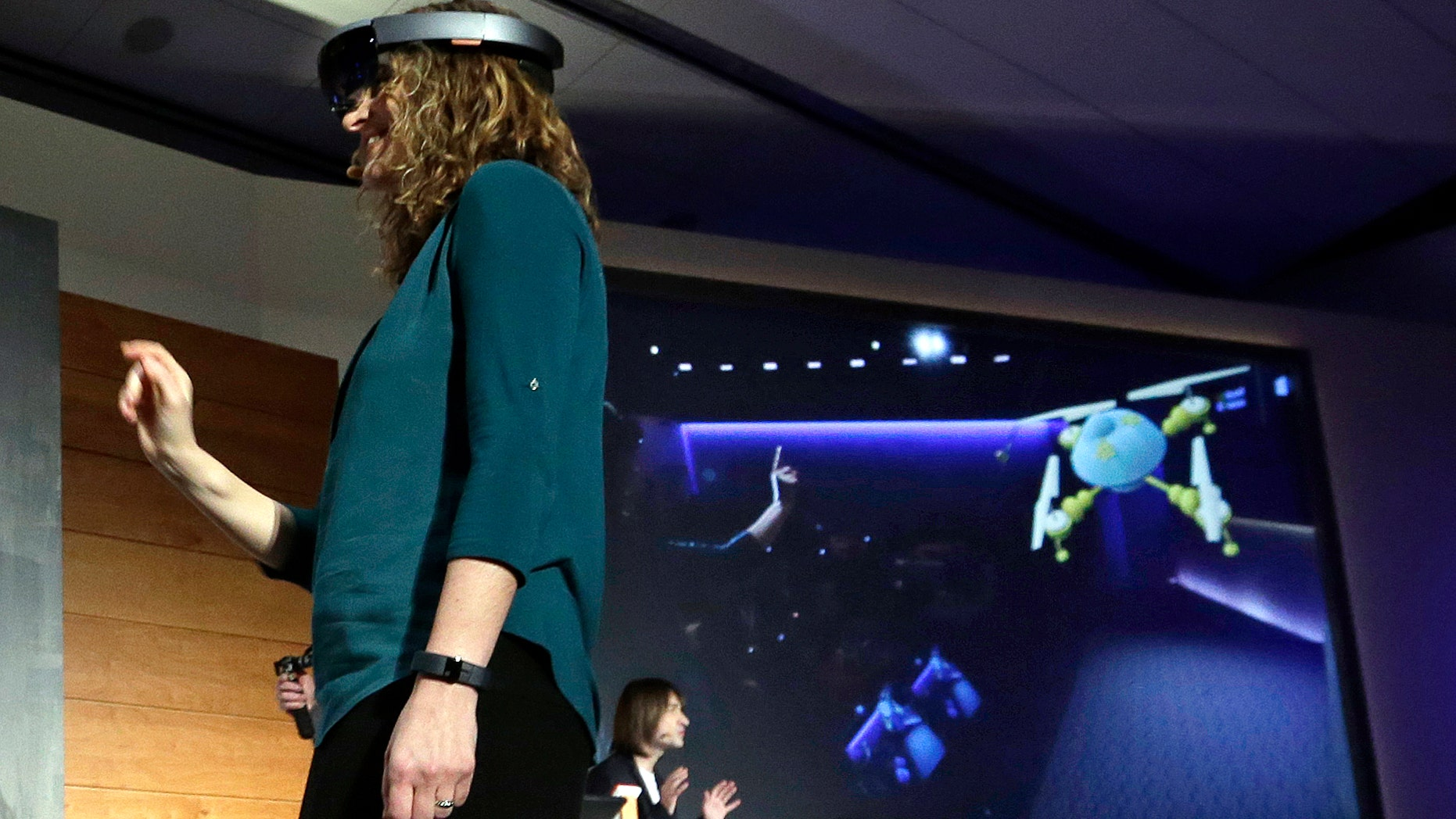 "In this photo taken Wednesday, Jan. 21, 2015, Microsoft's Lorraine Bardeen demonstrates a hologram device as what she ""sees"" is projected on a screen behind during an event at the company's headquarters in Redmond, Wash."
