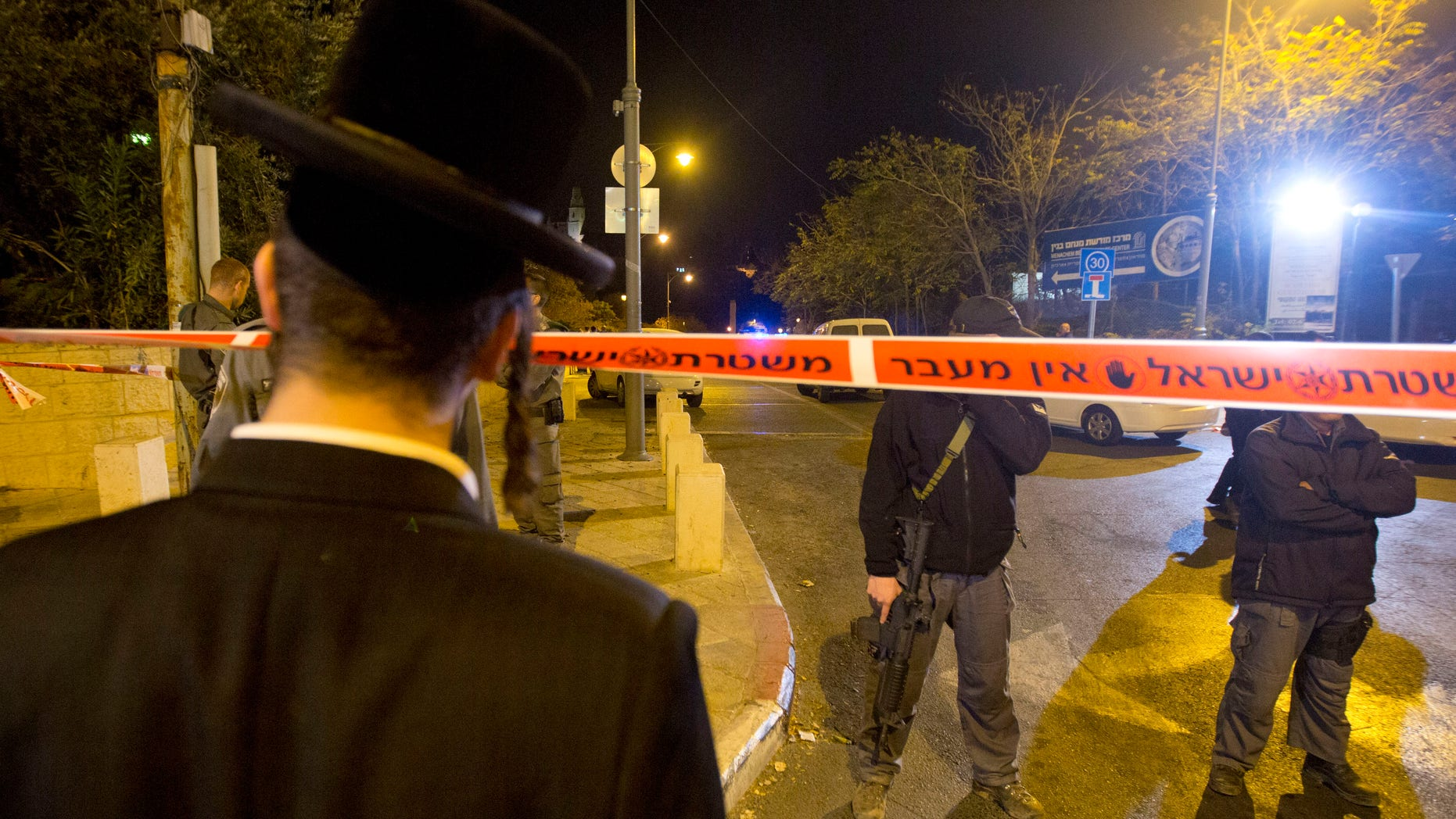 Oct 29, 2014: An ultra-Orthodox Jewish man looks as Israeli police officers stand guard at the scene of a shooting in Jerusalem