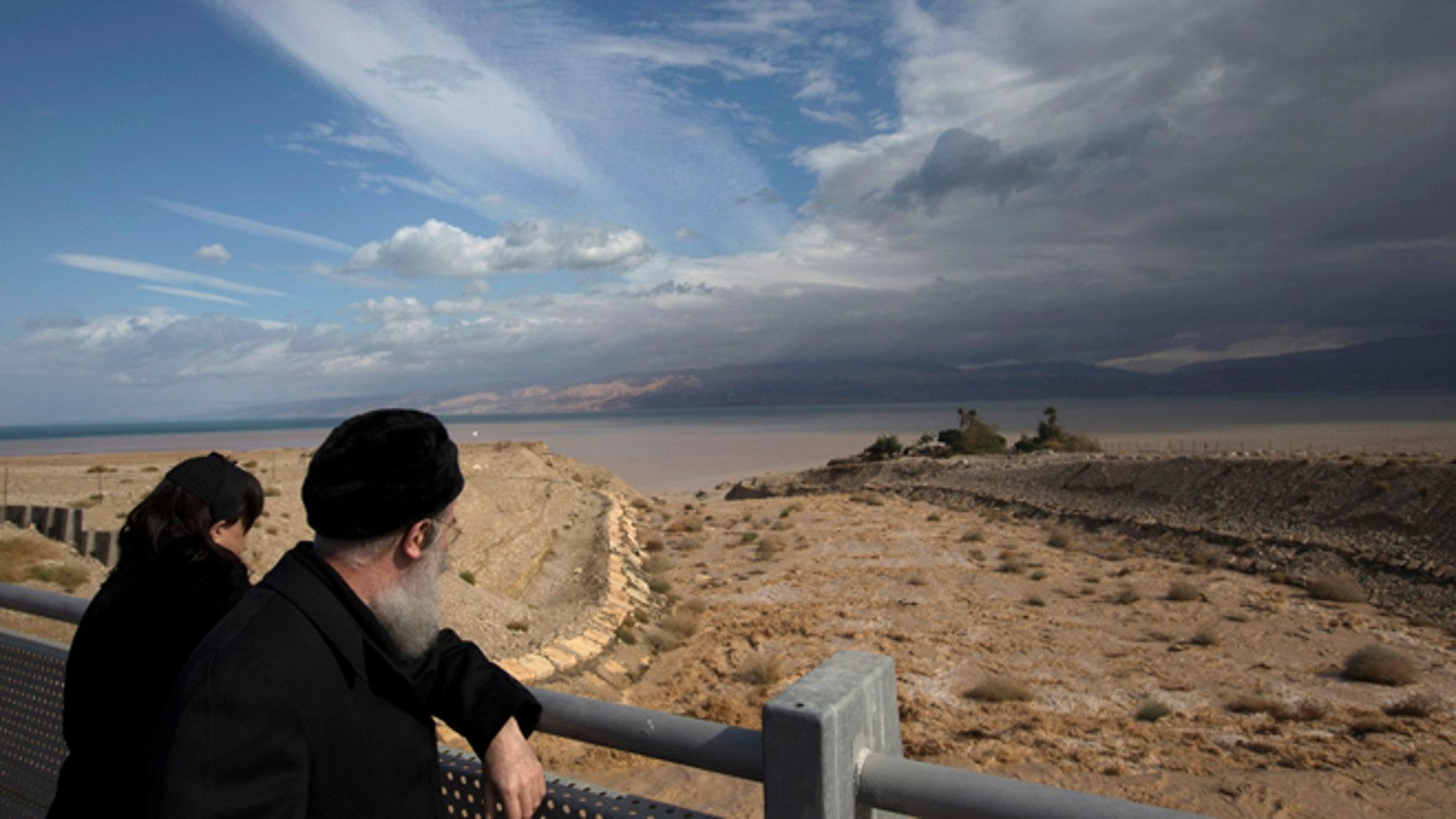 Jan. 9, 2013: A couple looks at water flowing into the Dead Sea during a flash flood near Kibbutz Ein Gedi.