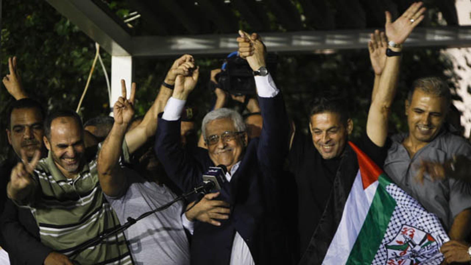 August 14, 2013: Palestinian President Mahmoud Abbas, center, waves with released Palestinian prisoners at his headquarters in the West Bank city of Ramallah. Israel released 26 Palestinian inmates, including many convicted in grisly killings, on the eve of long-stalled Mideast peace talks, angering families of those slain by the prisoners, who were welcomed as heroes in the West Bank and Gaza. (AP Photo)