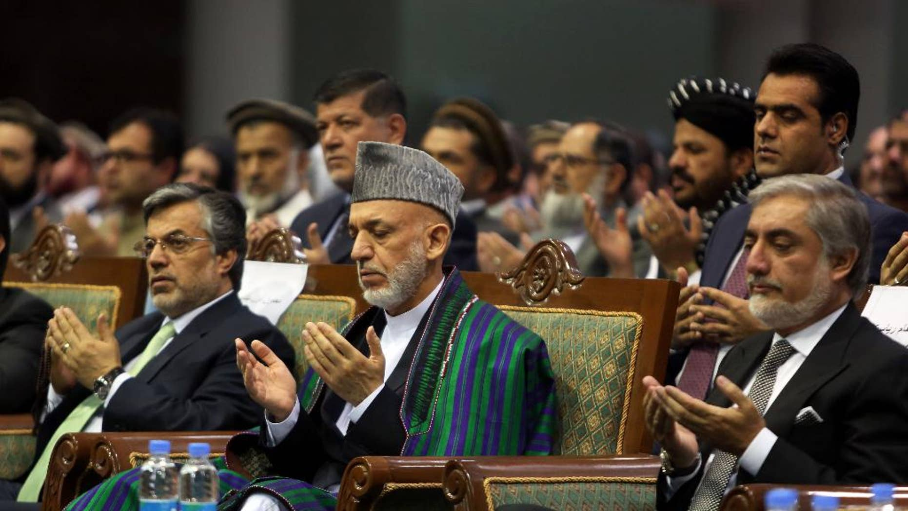 Afghan President Hamid Karzai, center, and Afghan presidential candidate Abdullah Abdullah pray during a ceremony marking the third anniversary of the assassination of former Afghan President Burhanuddin Rabbani in Kabul, Afghanistan, Saturday, Sept. 20, 2014. In 2011, an insurgent with a bomb wrapped in his turban assassinated Rabbani, who was leading a government effort to broker peace with the Taliban. (AP Photo/Rahmat Gul)