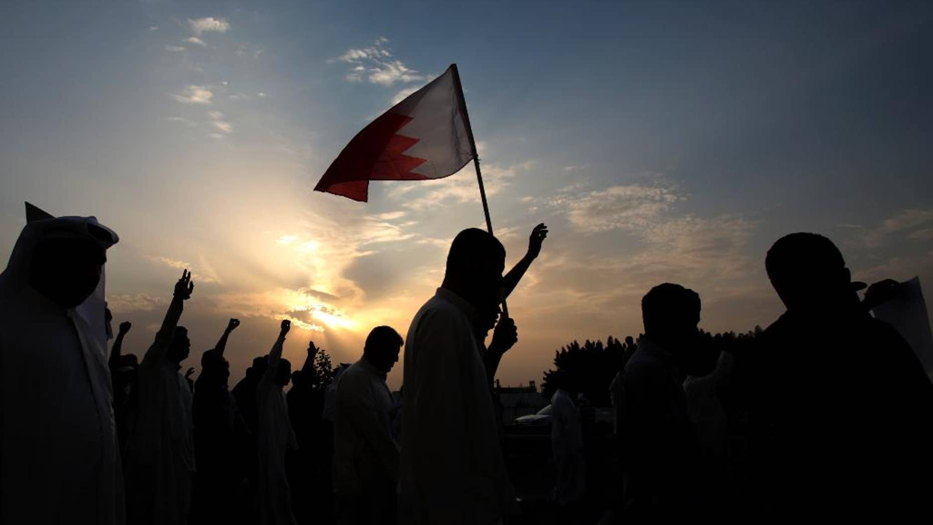Thousands of Bahraini anti-government protesters, waving national flags and gesturing defiantly, chant slogans during a march organized by opposition groups in A'ali, Bahrain, Friday, April 18, 2014. A pro-democracy uprising of peaceful daytime marches and violent nighttime clashes simmers in its fourth year in the Gulf island kingdom. (AP Photo/Hasan Jamali)