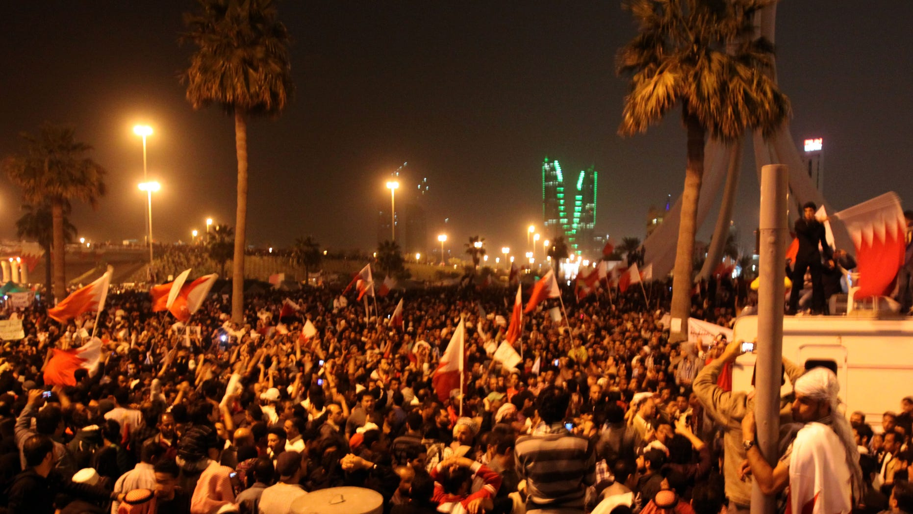 Feb. 16: Bahraini anti-government protesters wave flags in a demonstration at the Pearl roundabout, in Manama, Bahrain. In the background are the twin towers of the Bahrain Financial Harbour.