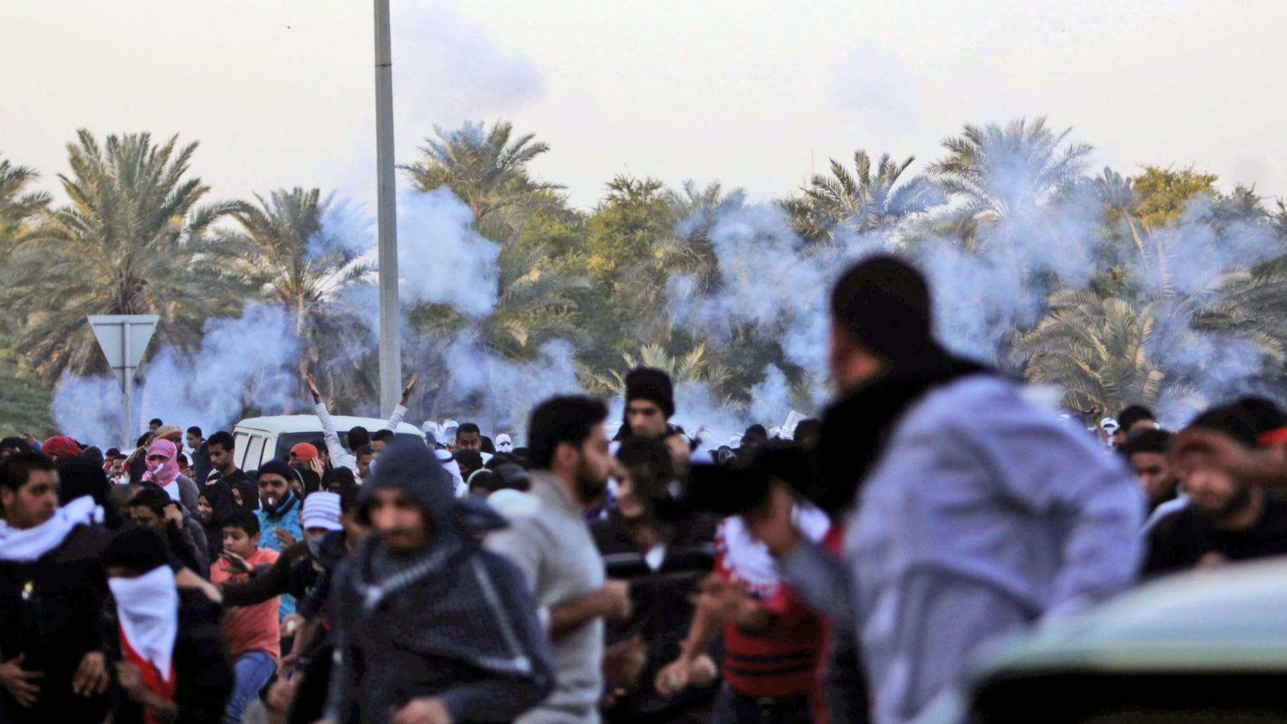DEc. 23, 2011: Anti-government protesters run as riot police begin firing tear gas.