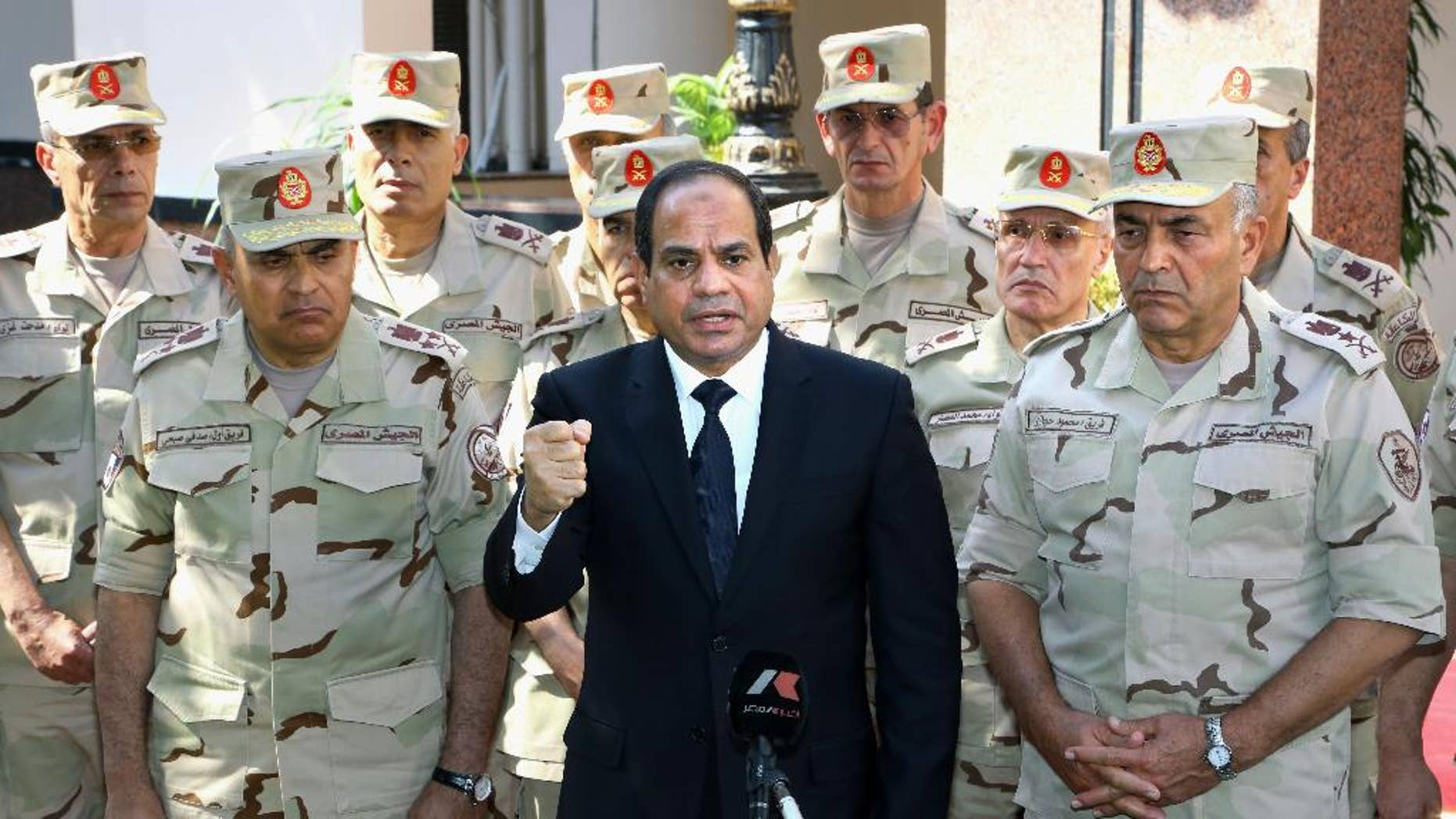 Egyptian President Abdel-Fattah el-Sissi, center, speaks in front of the state-run TV ahead of a military funeral for troops killed in an assault in the Sinai Peninsula, as he stands with army commanders in Cairo. (AP Photo/MENA, Mohammed Samaha)